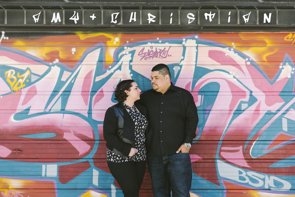 When Amy and Christian told me they met at a bookstore and would like to reflect that part of their relationship in their engagement photos, there was also another part of them that needed to be told as well. That's when we decided that shooting in Toronto's notorious Graffiti Alley would be a great fit in representing their relationship and personalities. We started the day at a second hand bookstore called Belfour Books on College. The store was filled from top to bottom of shelves full of interesting books on various types of subjects. These two naturally harmonize and complement each other so well that they didn't even plan on showing up in the same blue inspired matching outfits. That's how you know they are just made for each other!! Although it wasn't the exact bookstore of where they met, it ended up being a great backdrop to their engagement photos and an awesome representation of how their love story began. Next we headed down to the Graffiti Alley to continue taking some more pictures. Although it was quite a bright sunny day, the weather happened to be a little more on the cooler side of spring then we would of preferred. Luckily, Amy and Christian are two great champs who braved through the cool breezes all for the sake of art!! Since these two prefer city and urban places, Graffiti Alley ended up being a perfect place to capture this side of them. Plus its always great getting to take pictures in an environment that celebrates art and talent. We later walked back up Bathurst to visit this beautiful mural located alongside Alexandria Park. That's when Amy and Christian decided to bust out the hilariously adorable matching wedding date shirts Amy's aunt got them for Christmas. What a fun way to wrap up an adventurous day walking around. Looking forward to seeing these two again at their wedding!