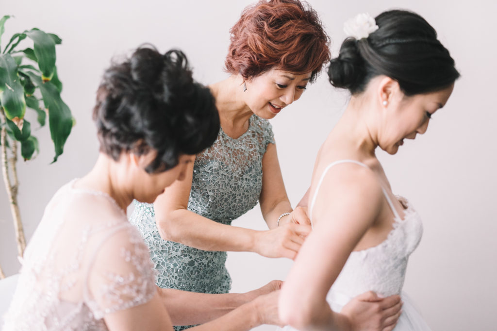Mothers helping bride get ready