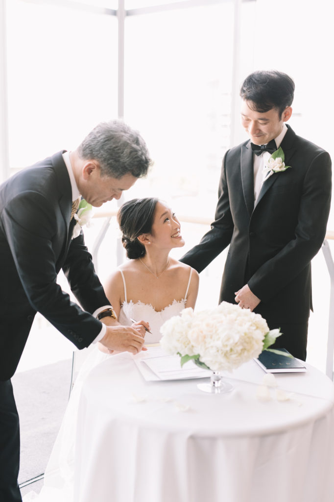Bride looking up at groom signing certificate