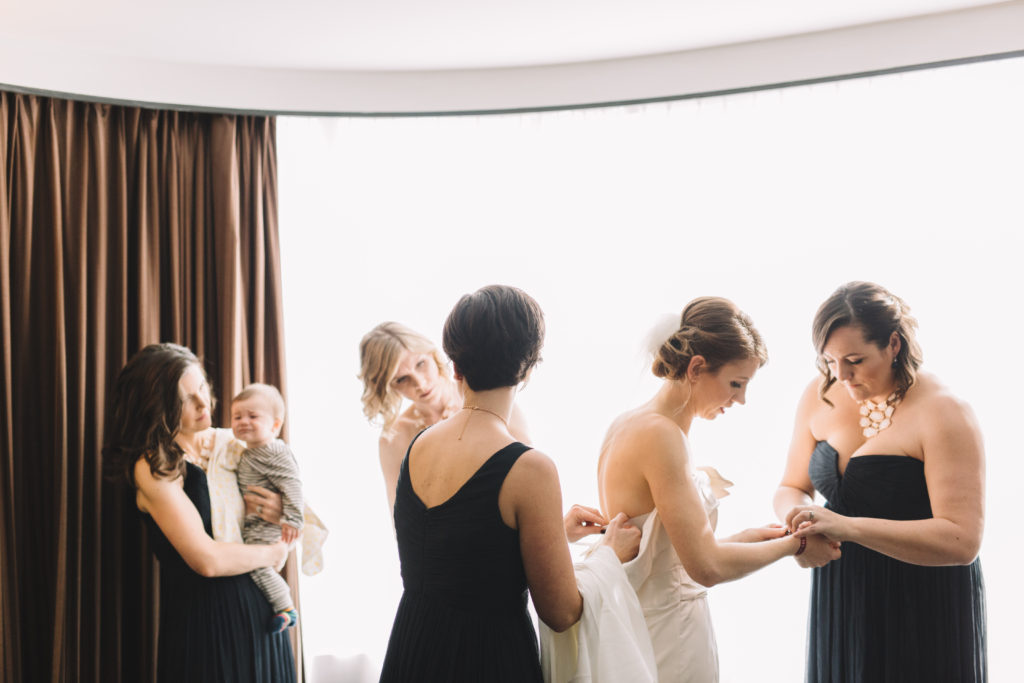 Bride getting dressed with the help of bridesmaids