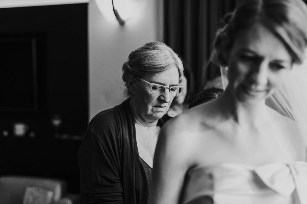 Mother of the bride helping bride get into wedding dress