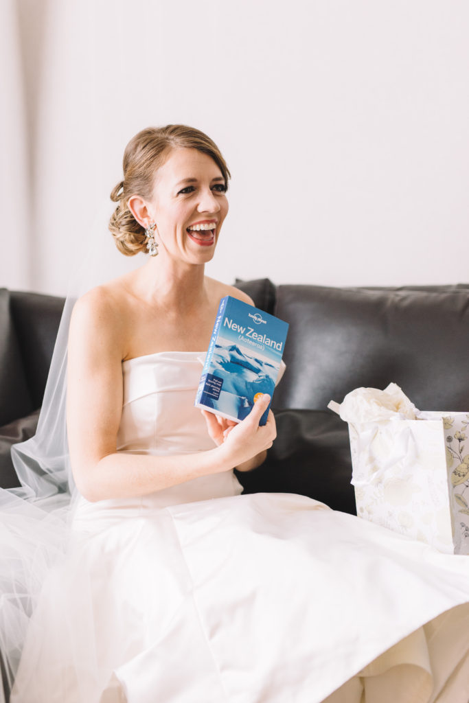 Bride laughing as she opens groom's present