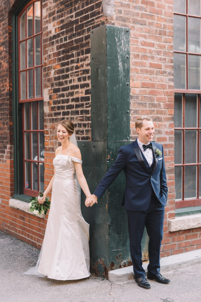 Bride holding hands with groom before first look