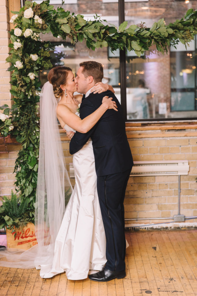 Groom kissing his bride during ceremony