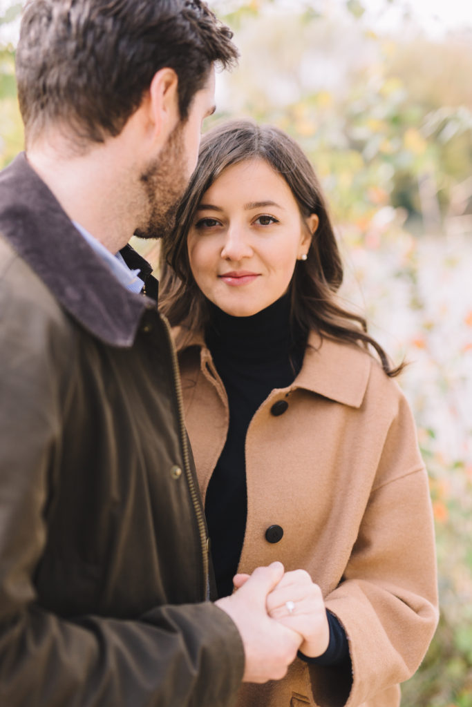 Man holding his Fiance's hand while she looks at camera