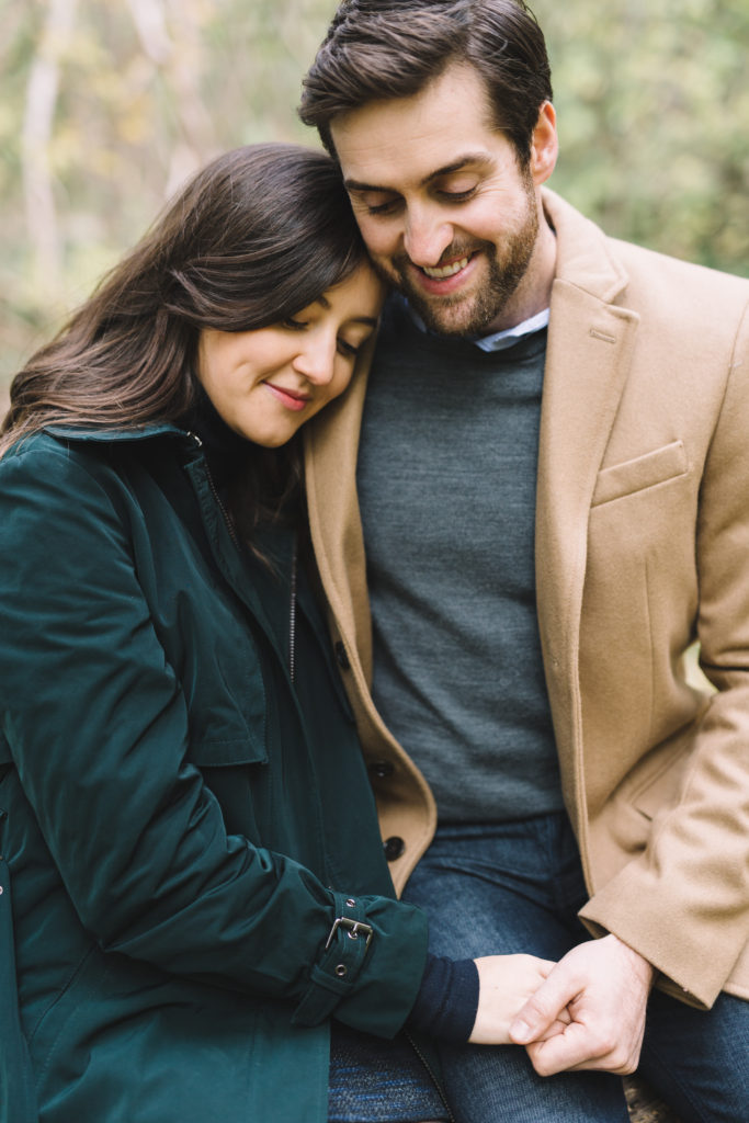 Couple cuddling and and holding hands in Mill Pond Engagement Session