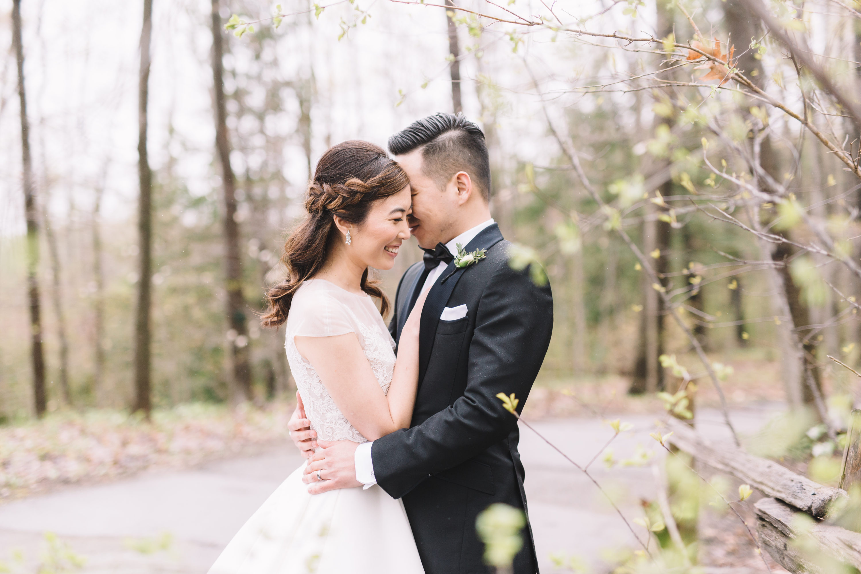 Bride and groom snuggling in rainy forest at Whistle Bear Golf Club