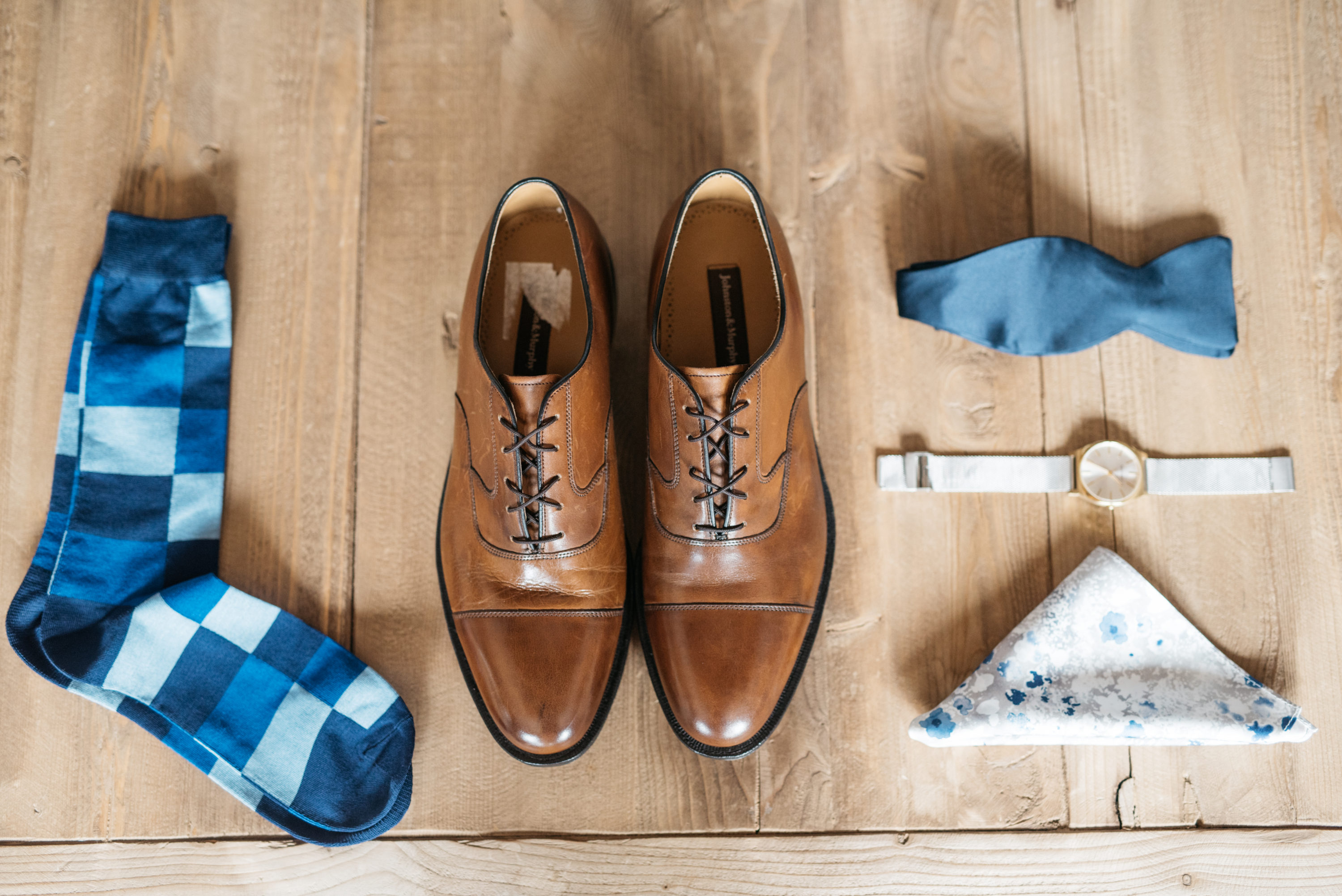 Groom details of his shoes, socks, watch, and bow tie