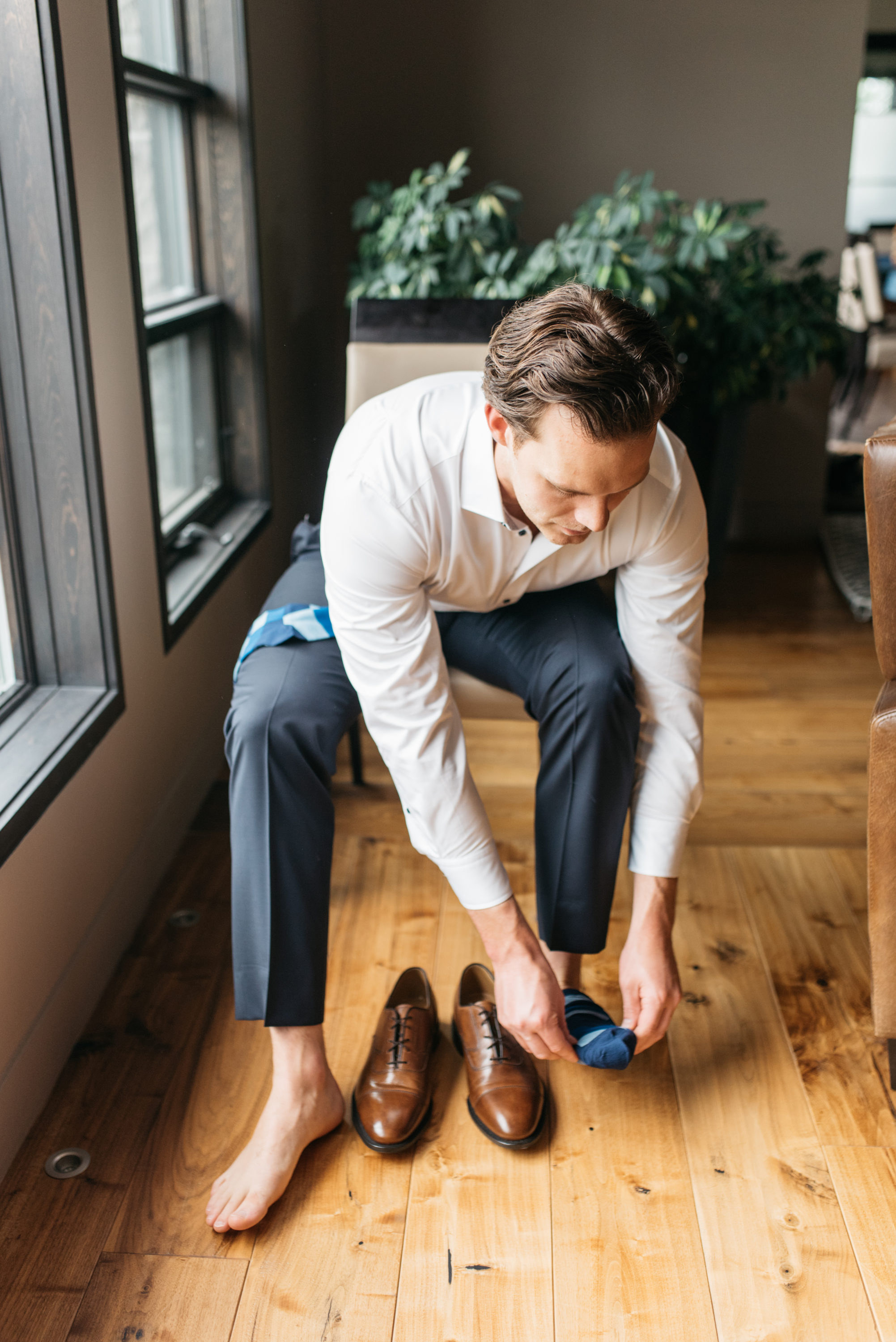 Groom putting on his shoes for wedding at Arlington Estate