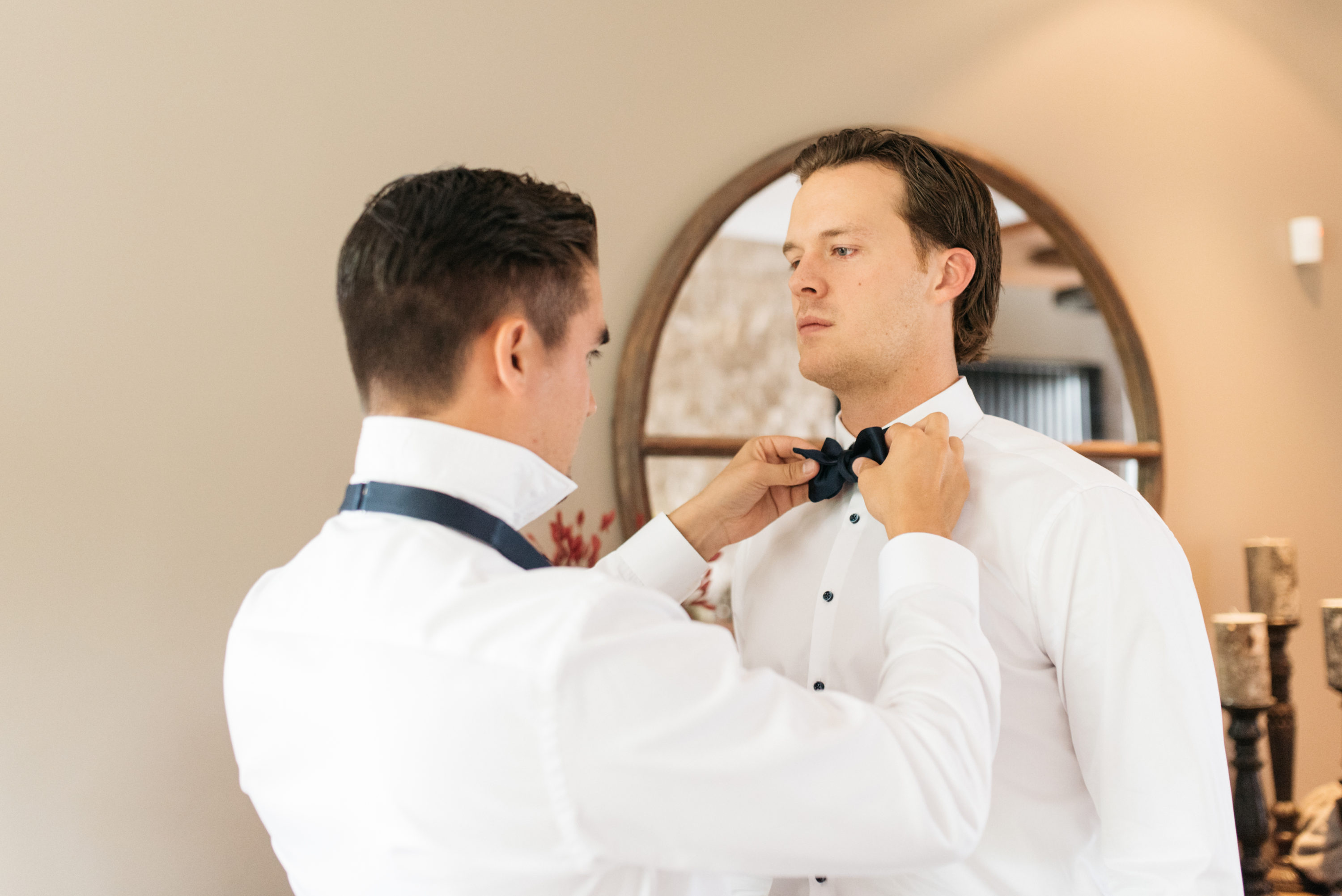 Groomsman helping groom out with his tie