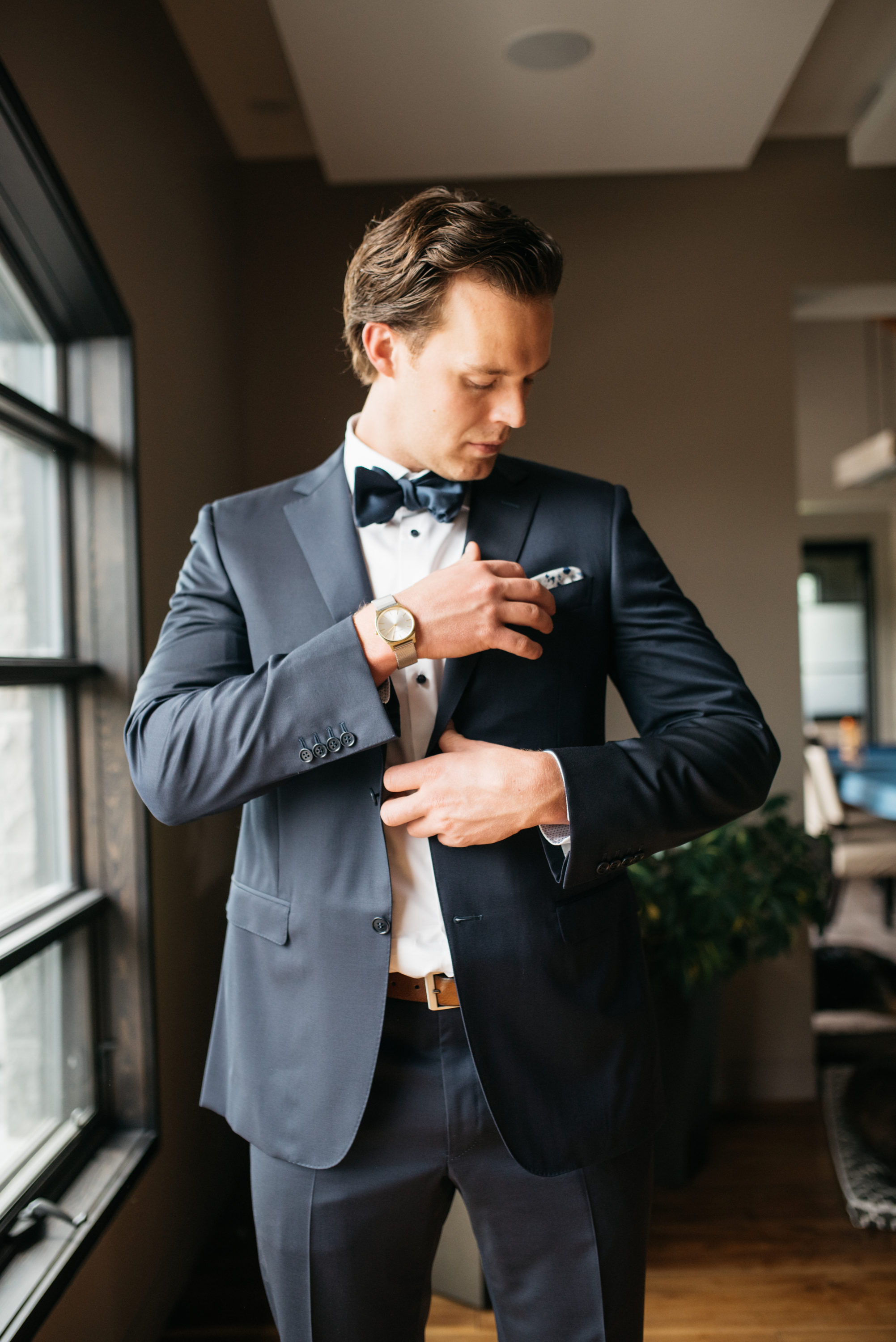 Groom putting his pocket square on