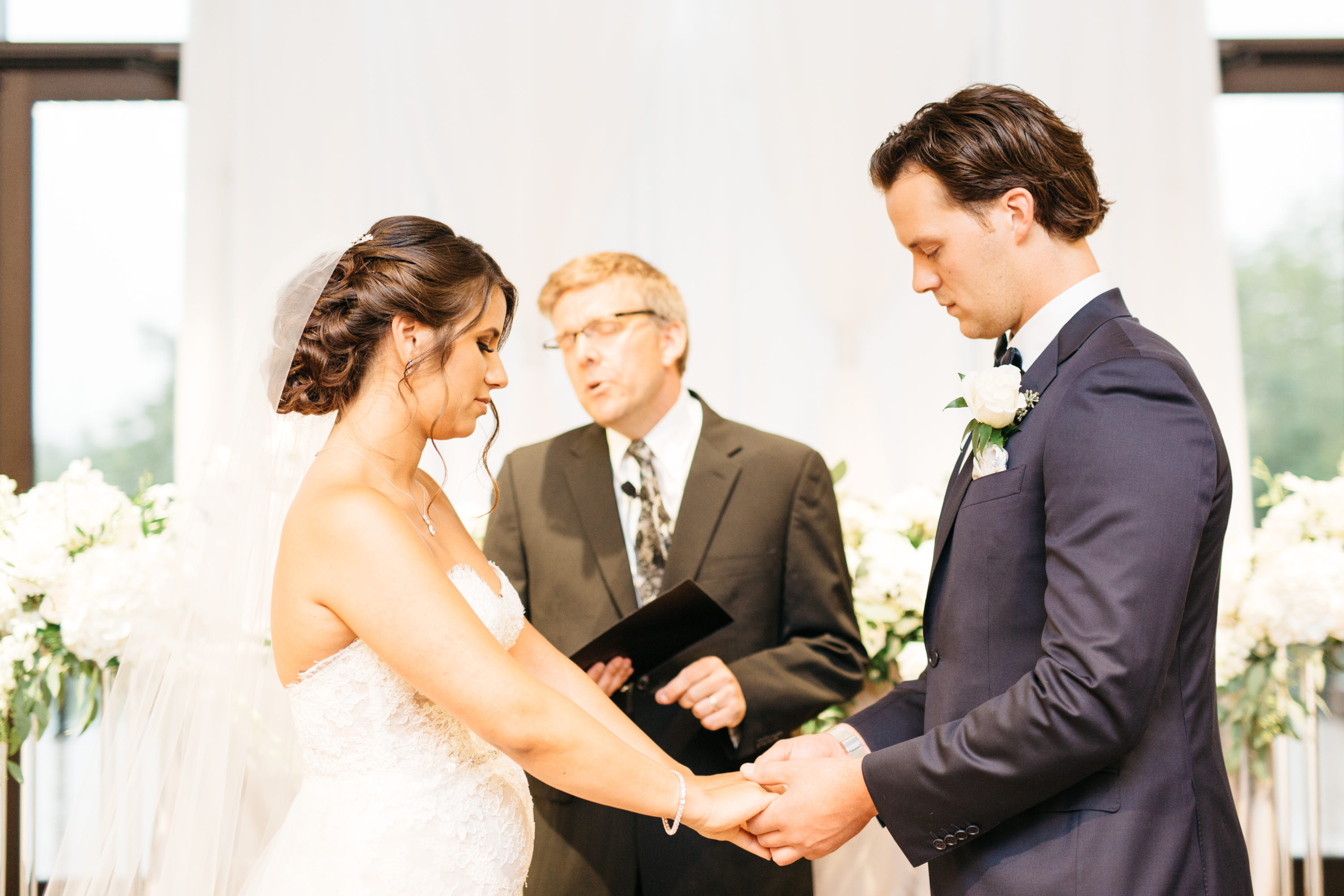 Bride and groom holding hands during their ceremony