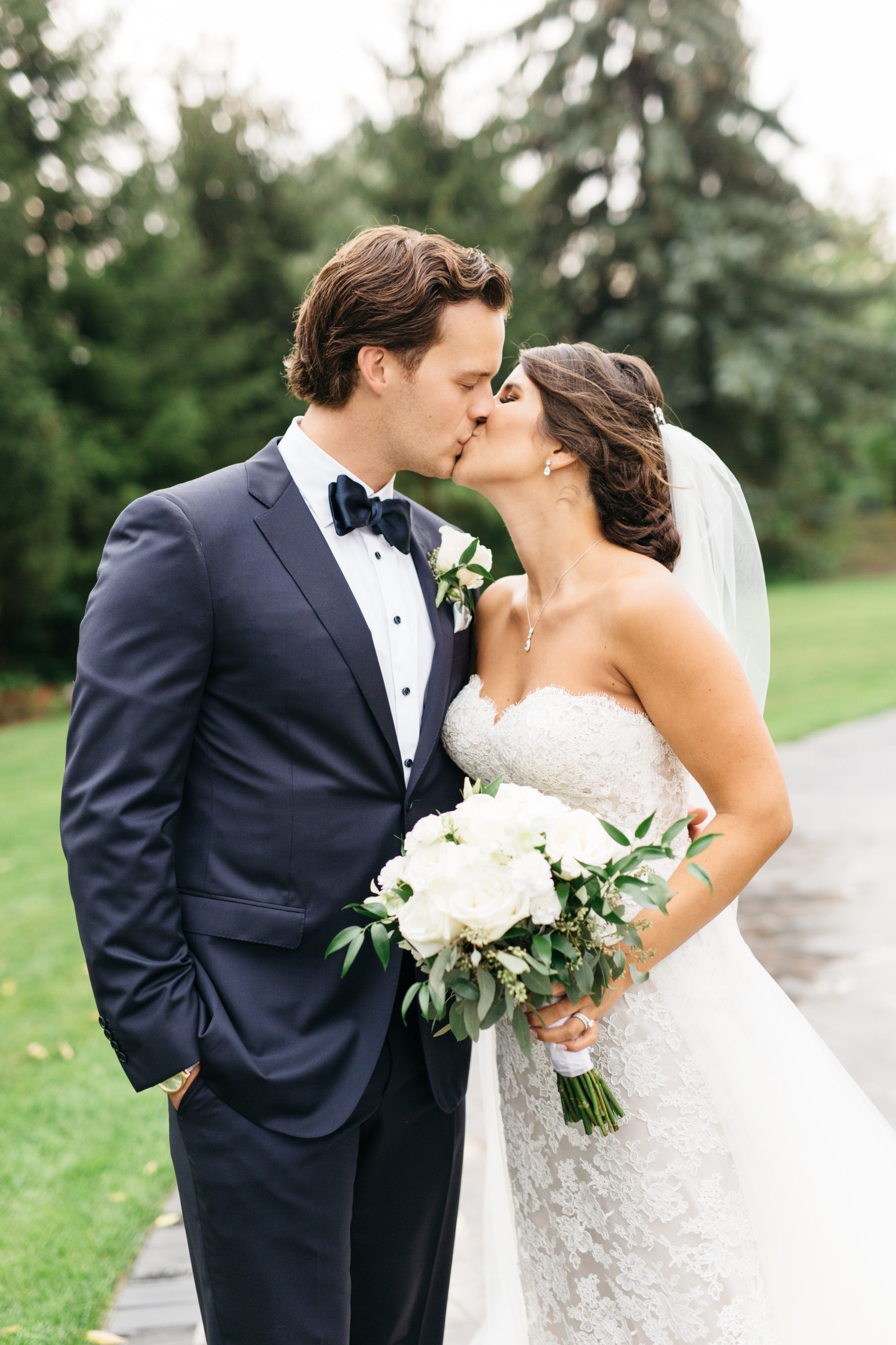 Bride and groom kissing during wedding photos