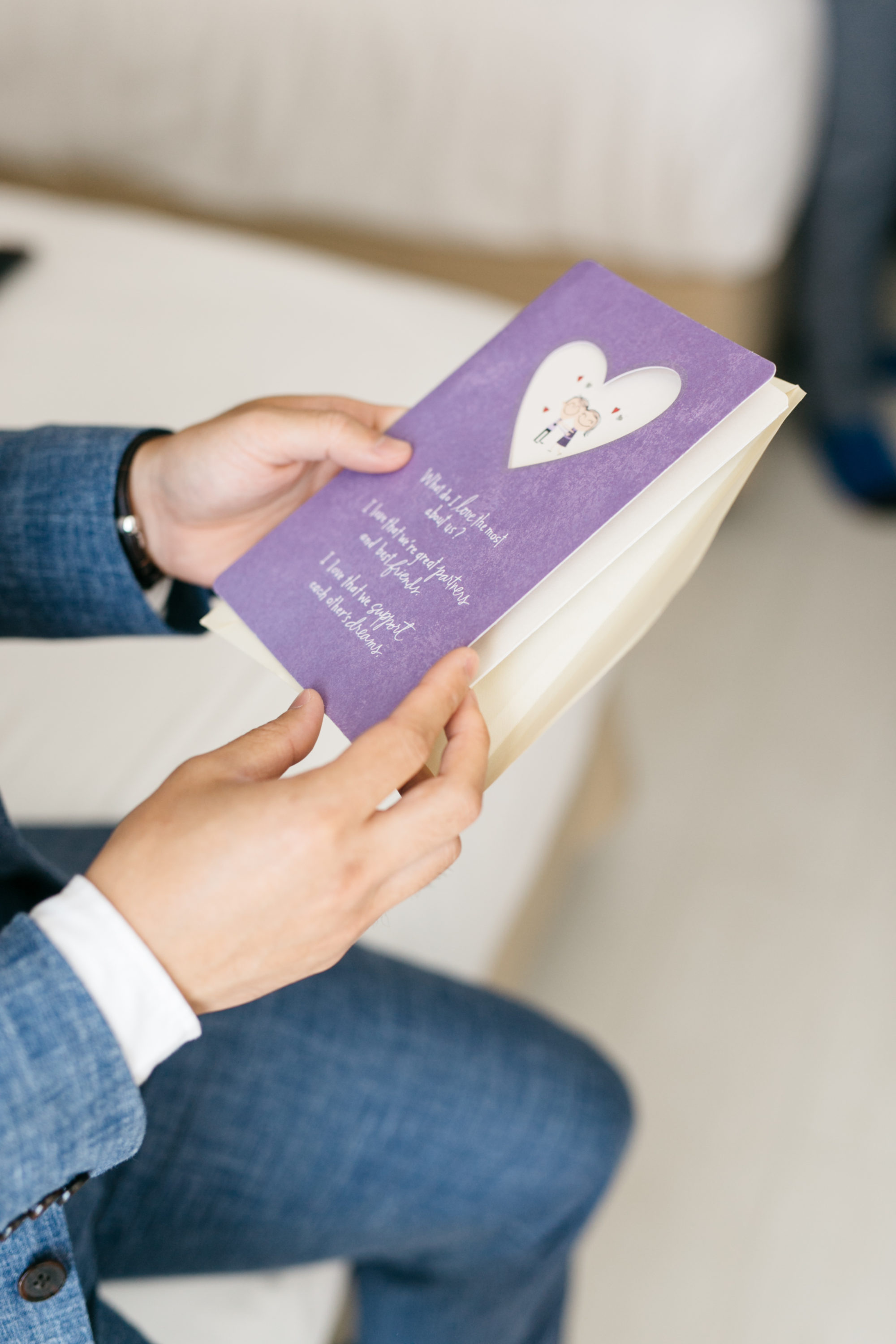 Groom opening up wedding card from bride