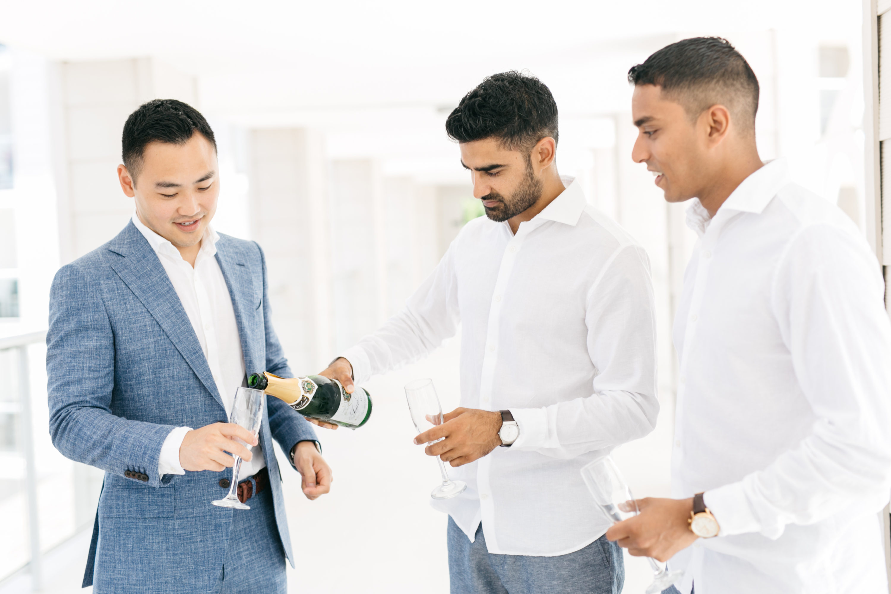 Groomsmen pouring champagne