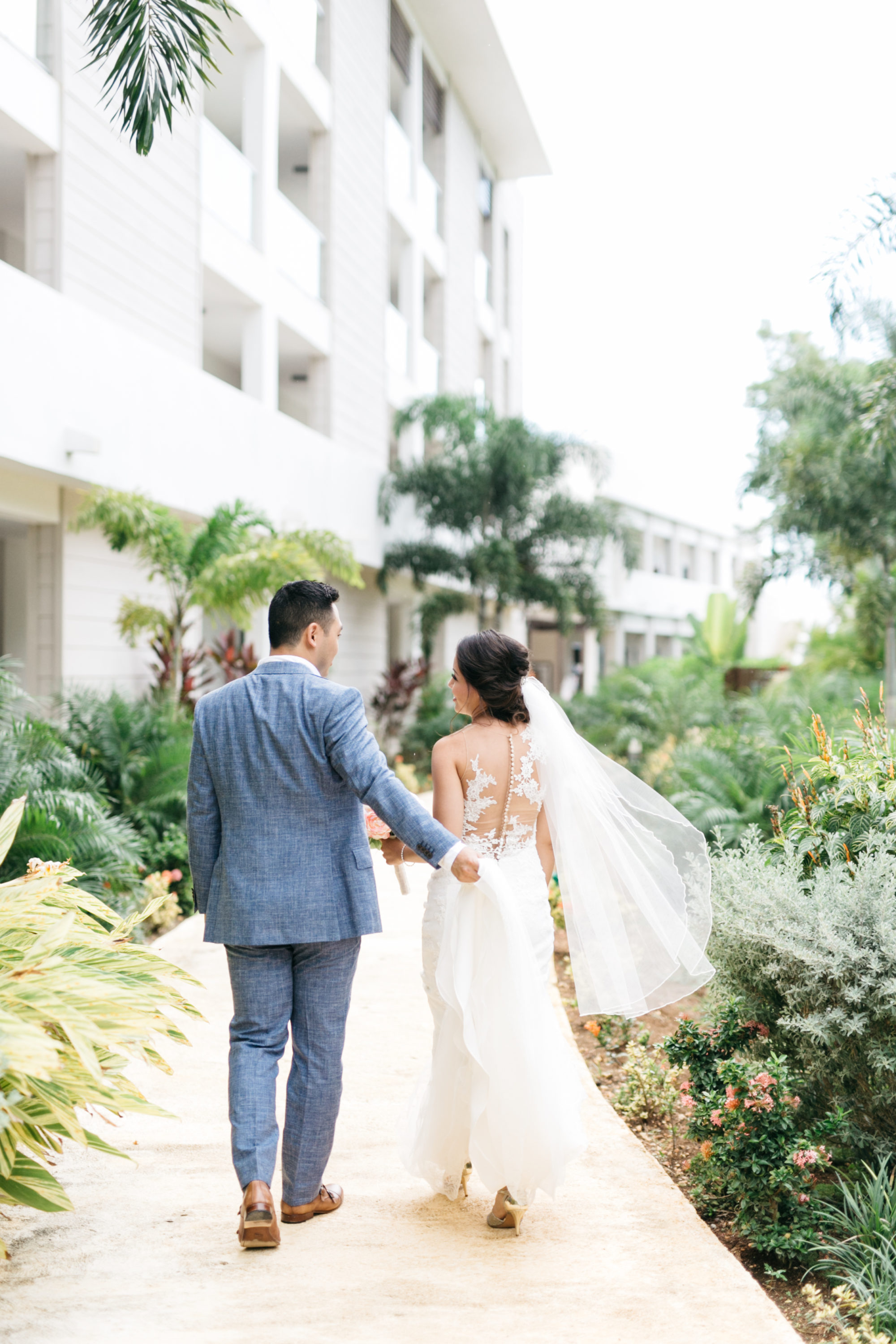 Bride and groom walking through The Royalton White Sands Resort