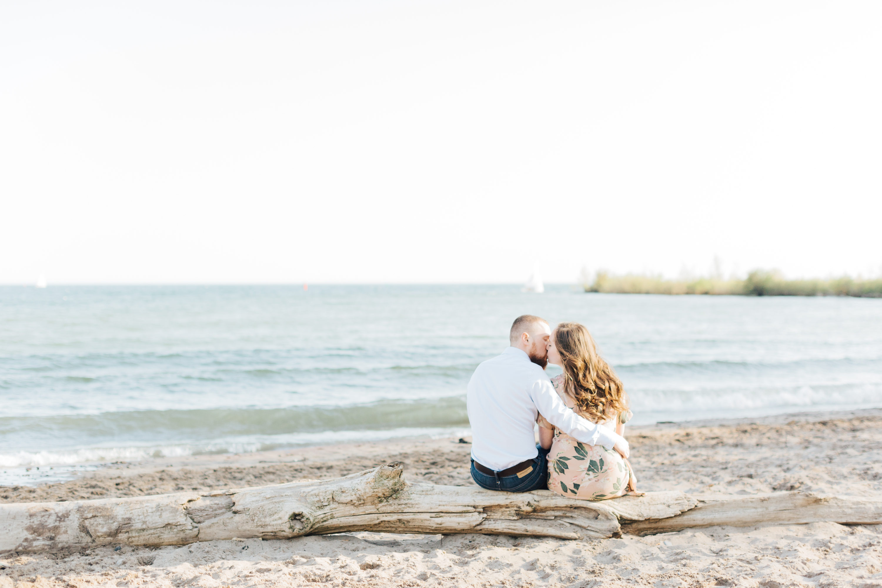 Couple sitting and kissing at Cherry beach for engagement photos