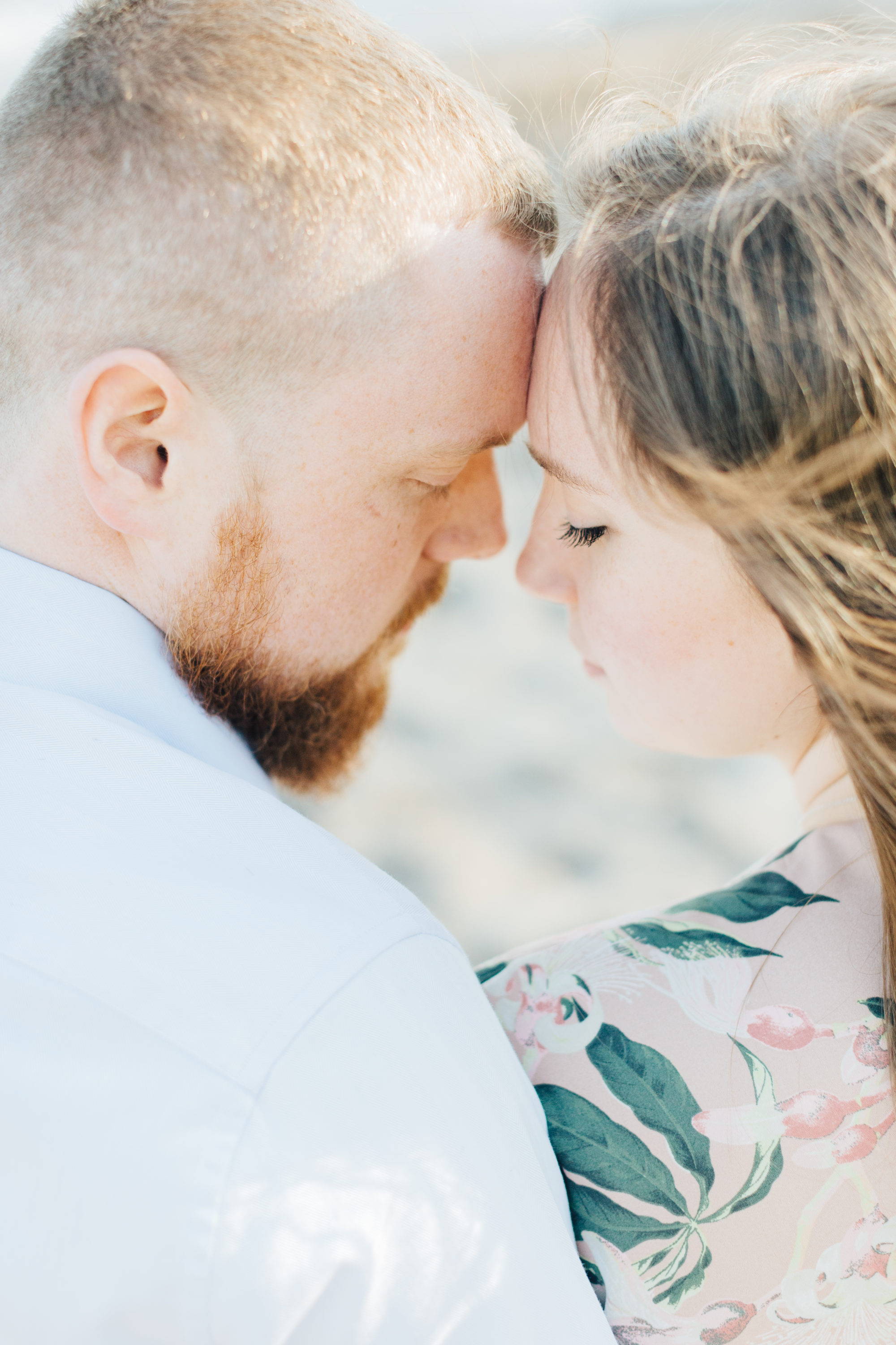 Couple cuddling at engagement session at cherry beach
