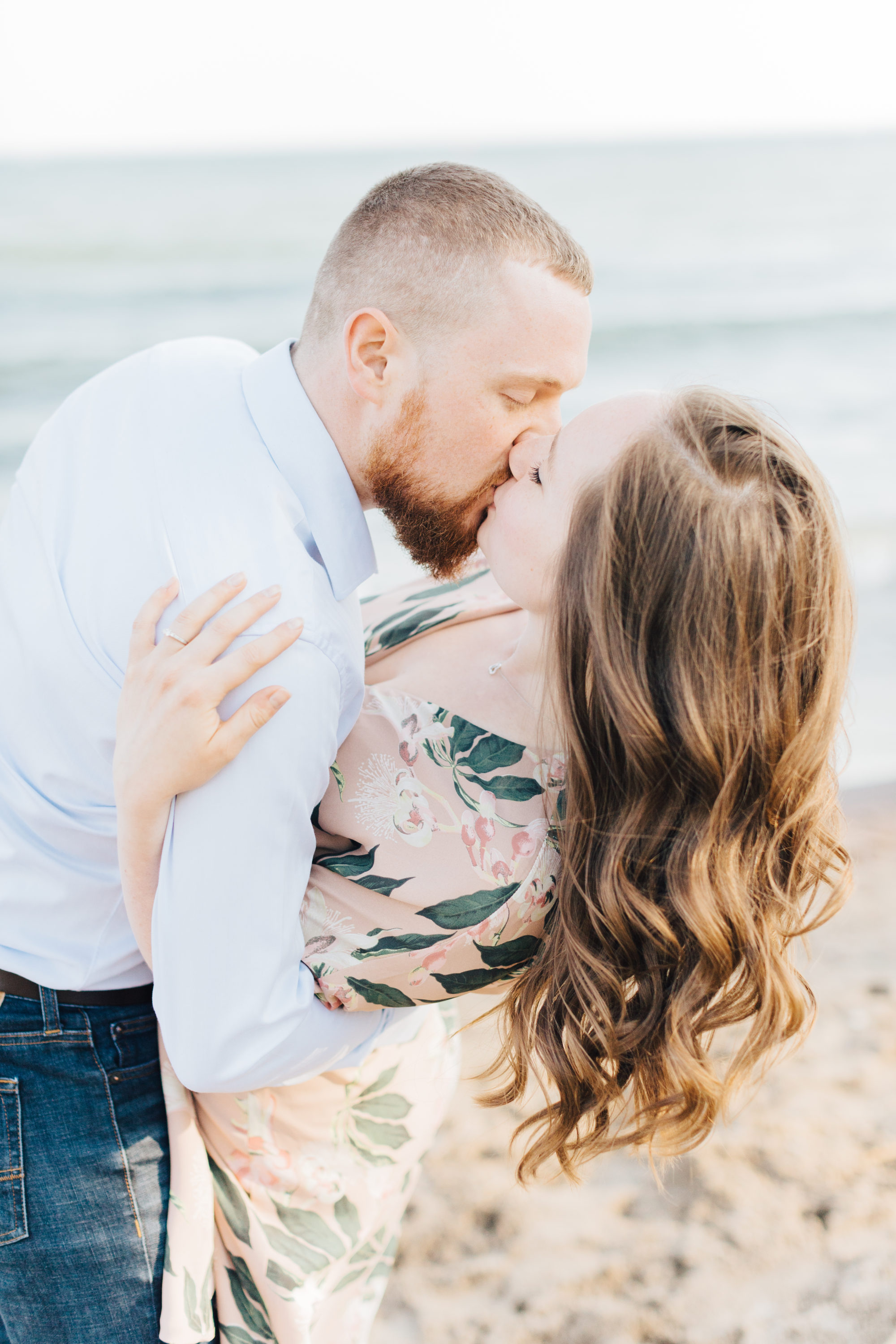 Couple kiss at engagement session at cherry beach