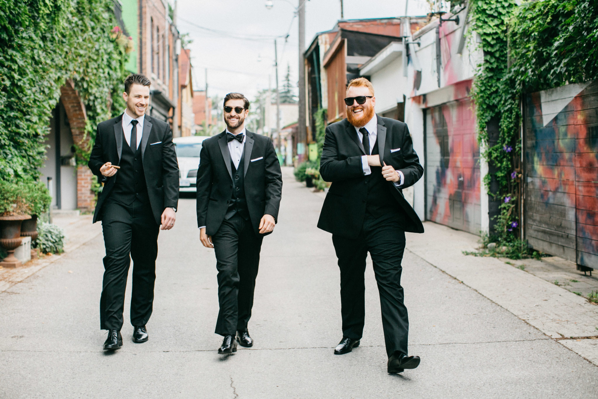 Groom and groomsmen walking down graffiti alley in Toronto