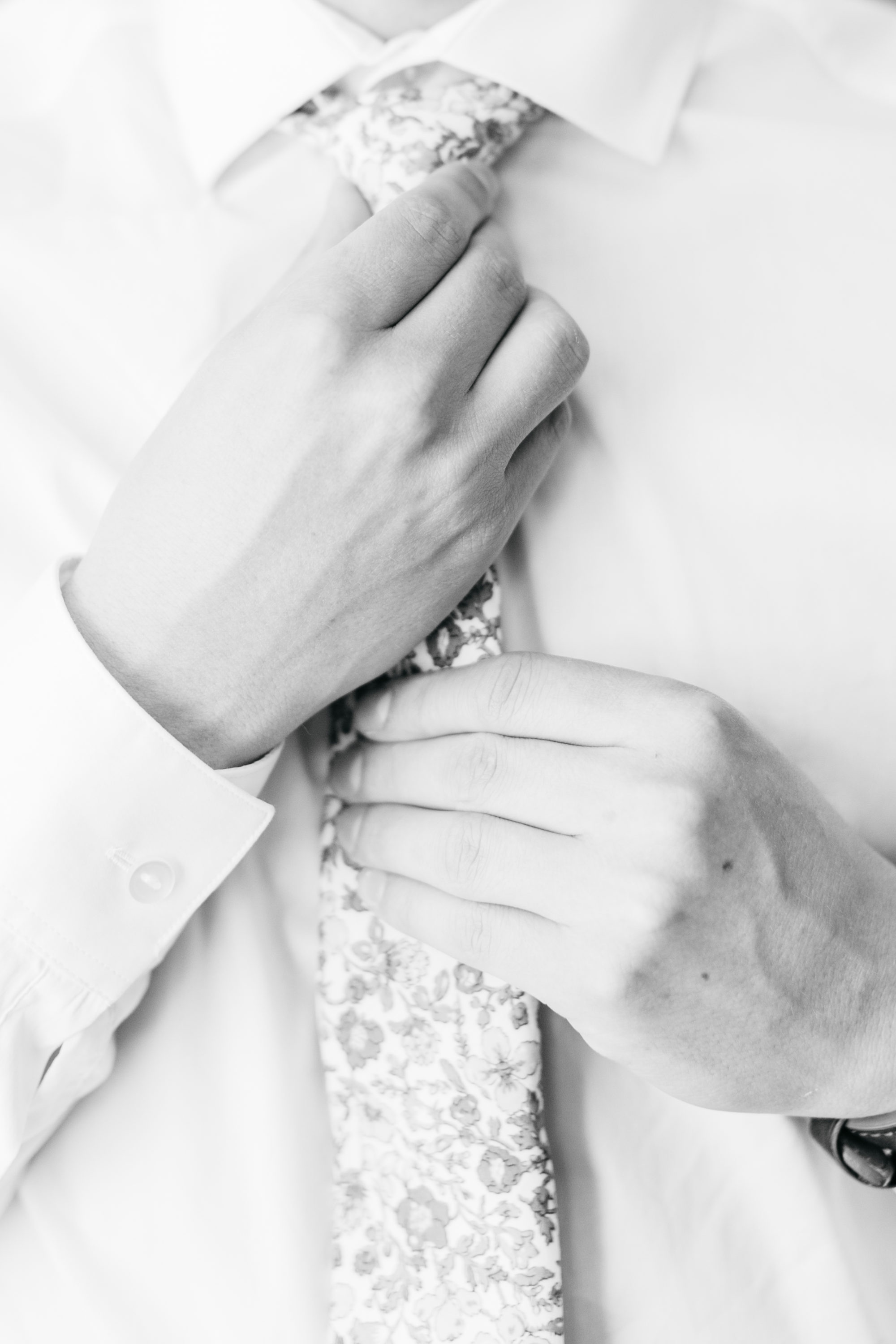 Close up of groom fixing tie