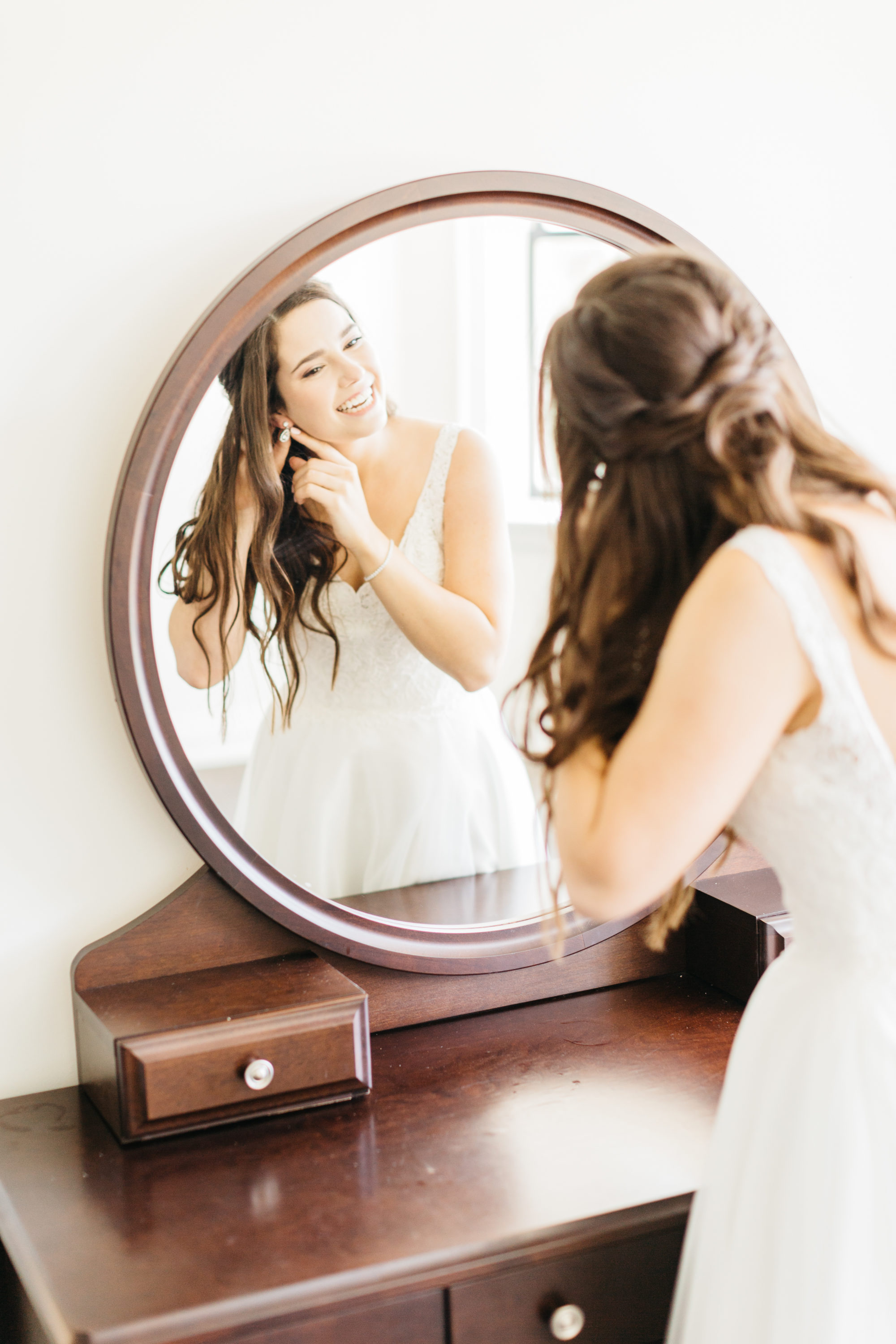 Bride putting on her earrings in bridal suit at Harding Waterfront Estate