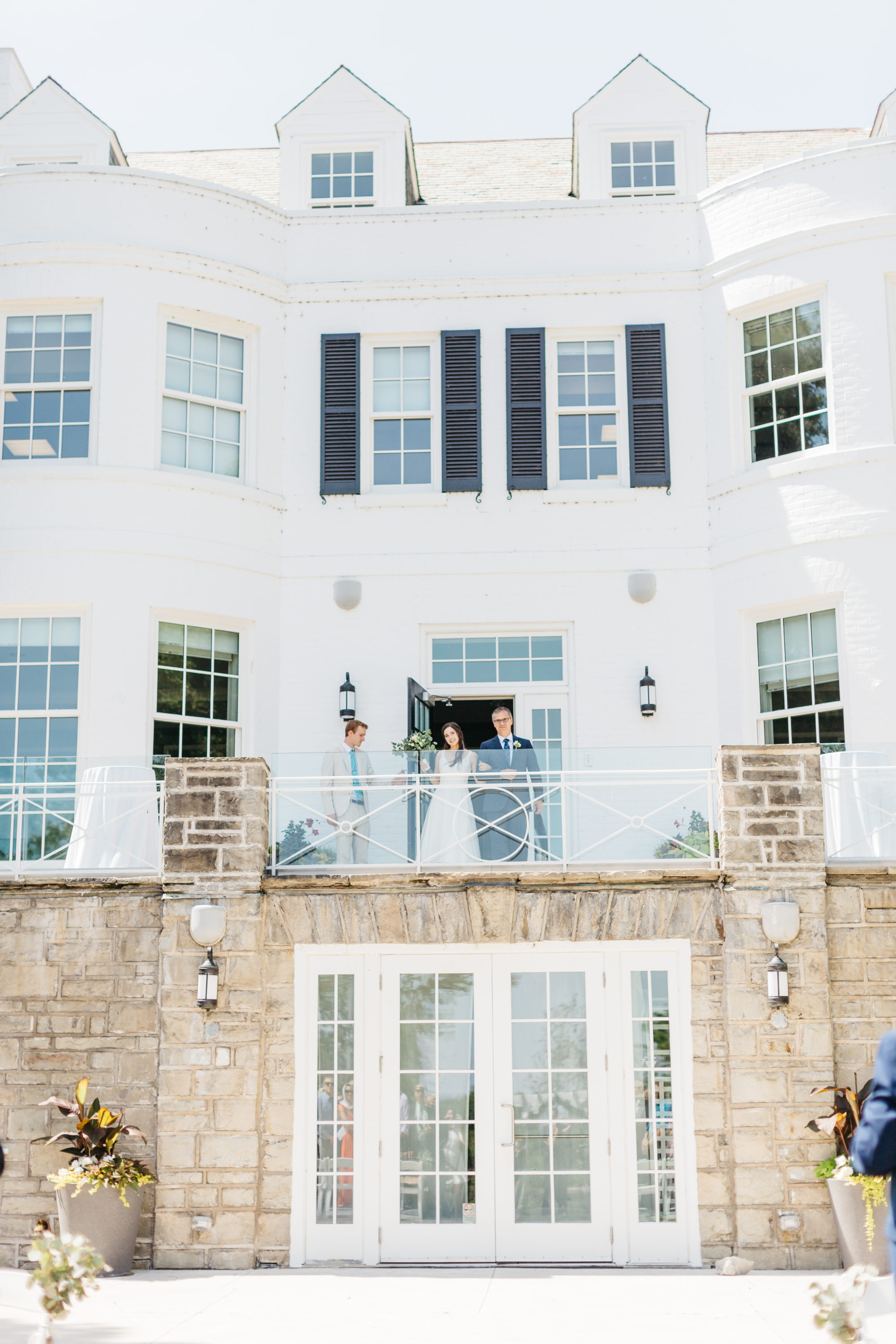 Bride exiting Harding Waterfront Estate balcony at ceremony