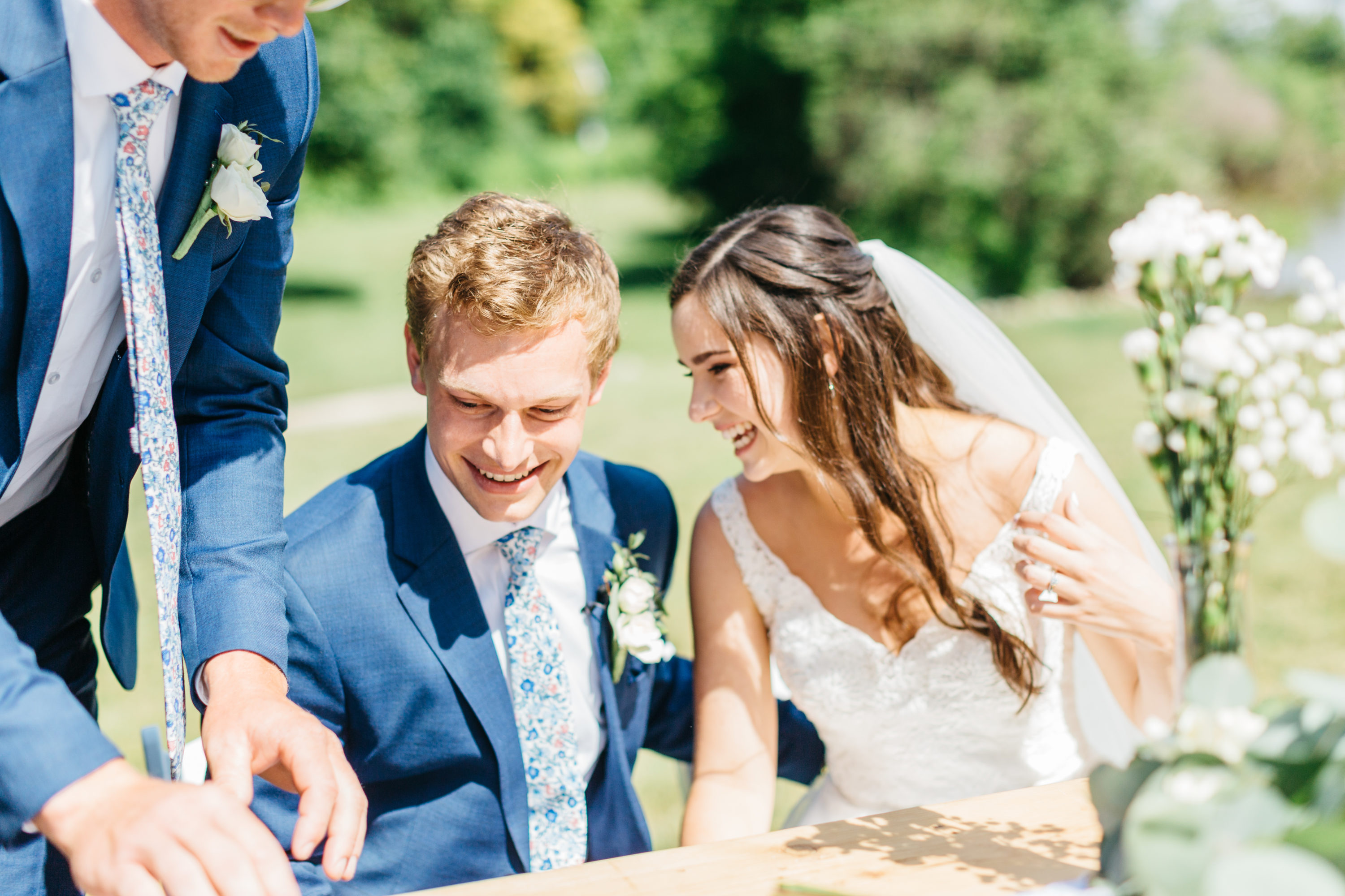 Bride laughing with groom as he signs marriage license