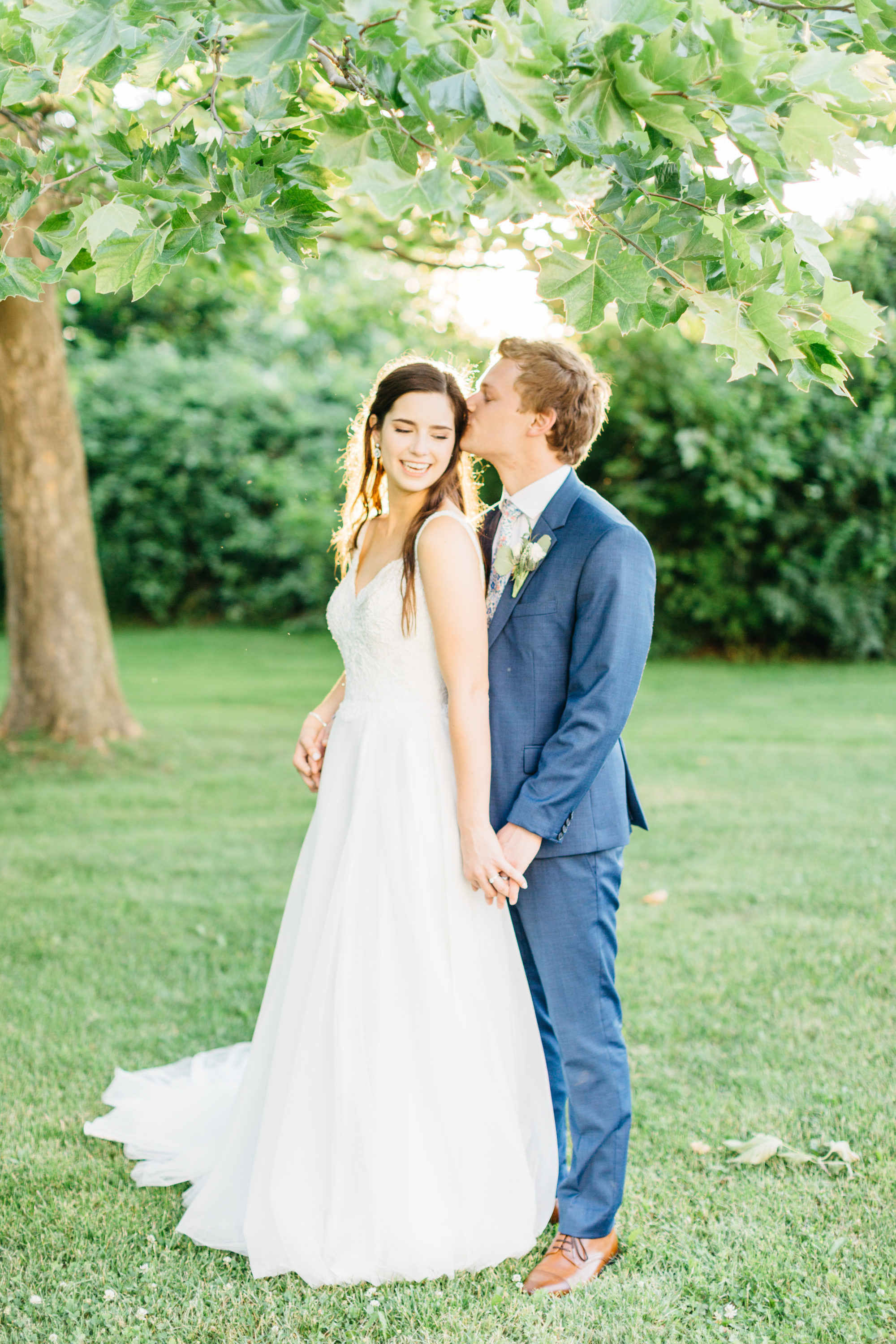 Bride and groom kissing under tree at Harding Waterfront Estate