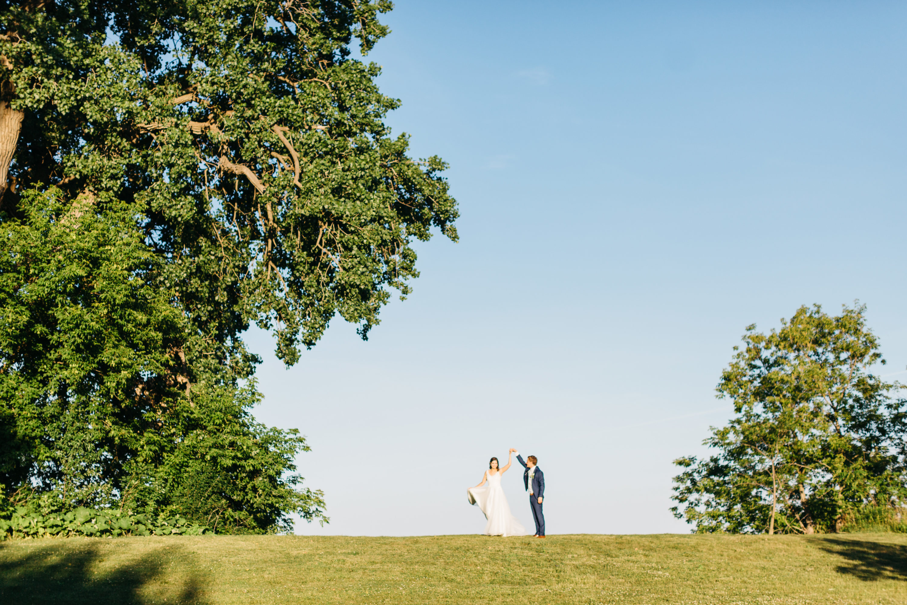 Bride and groom dancing on top of hill at Harding Waterfront Estate