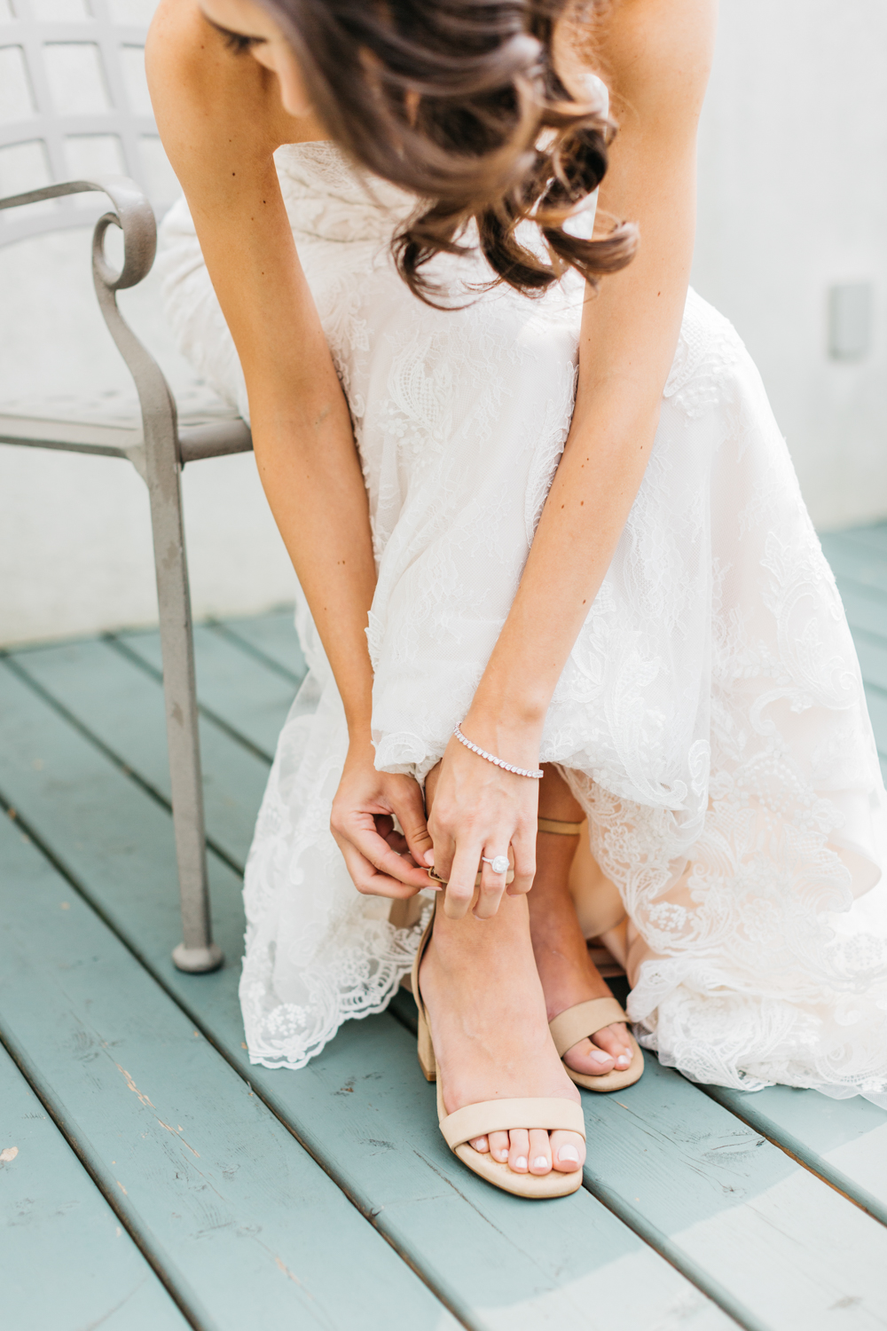 Bride putting on shoes outside at Riverbend Inn