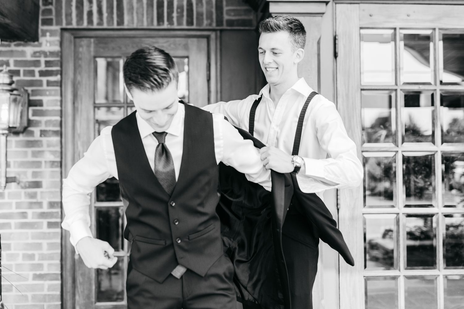 Groomsman helping groom put on jacket