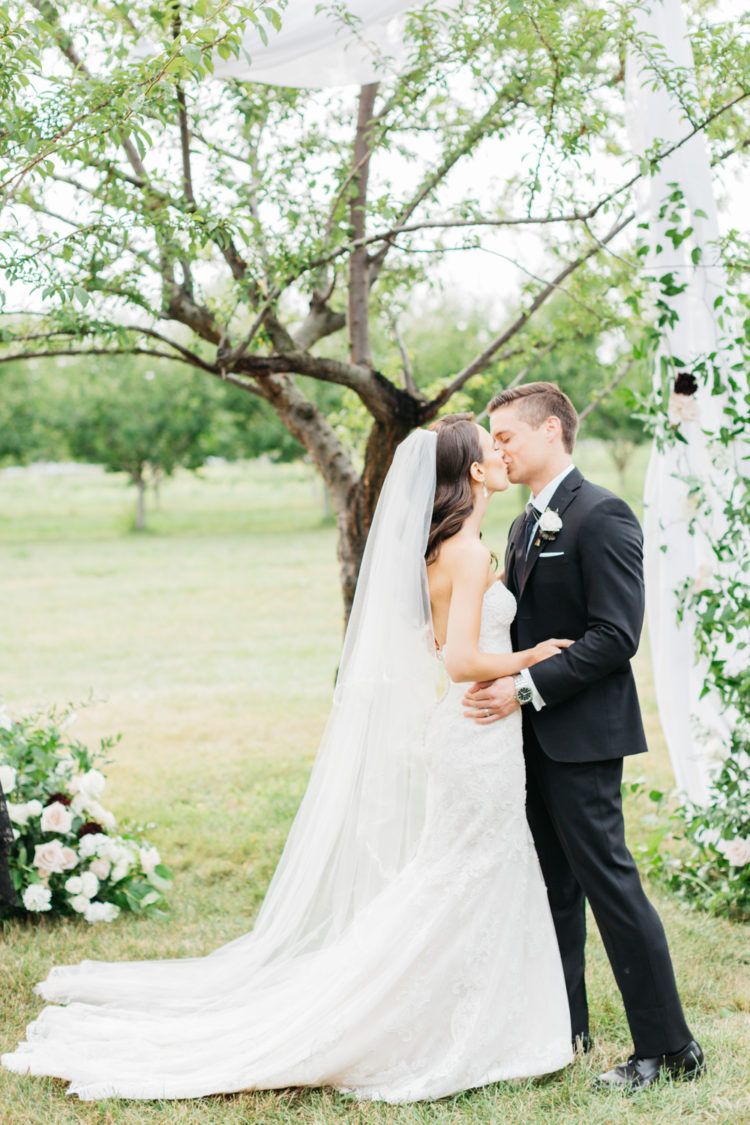 Bride and groom first kiss at Kurtz Orchard Market place