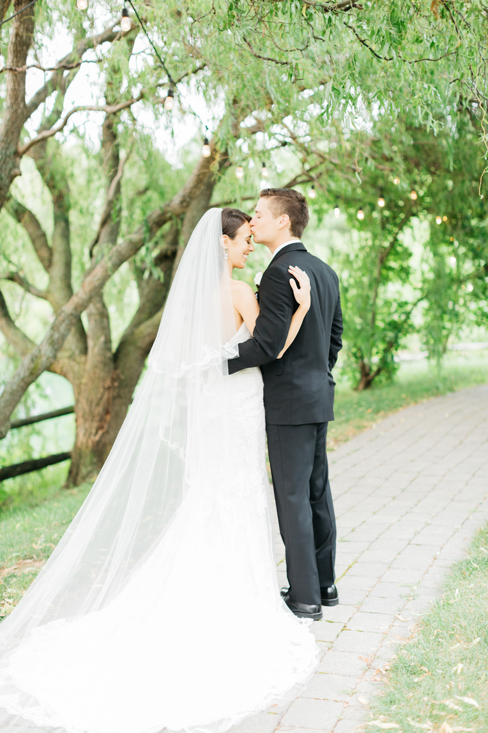 Groom kissing brides head