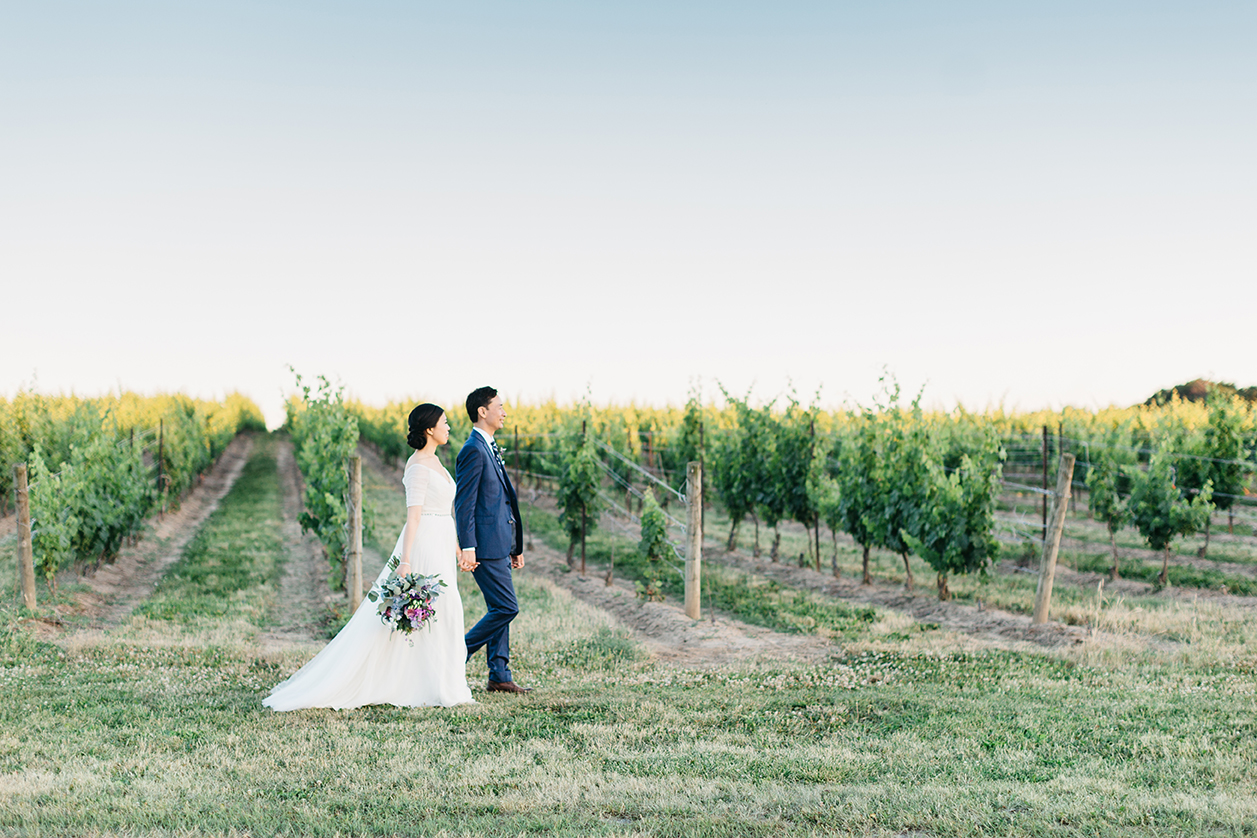 Bride and groom walking vineyards at Sue Ann Staff Estate Winery