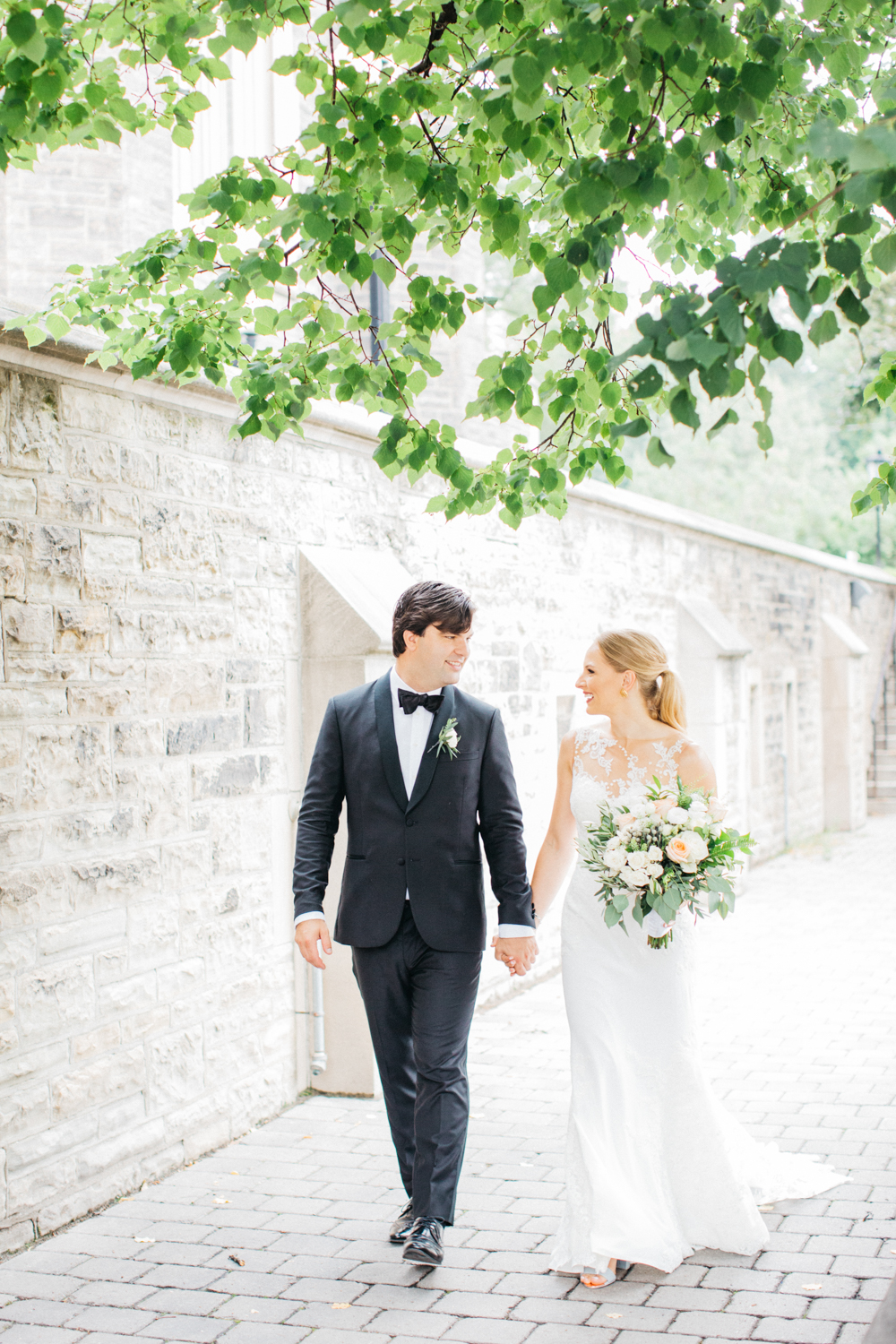 Bride and groom walking hand in hand at Hart House in Toronto