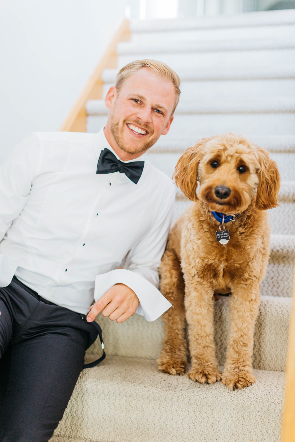 Groom smiling with his puppy on wedding day in Hamilton