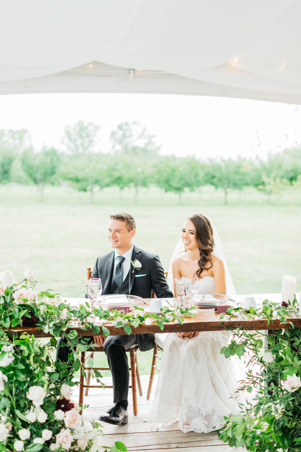 Bride and groom listening during speeches at their Kurts Orchard Marketplace Wedding