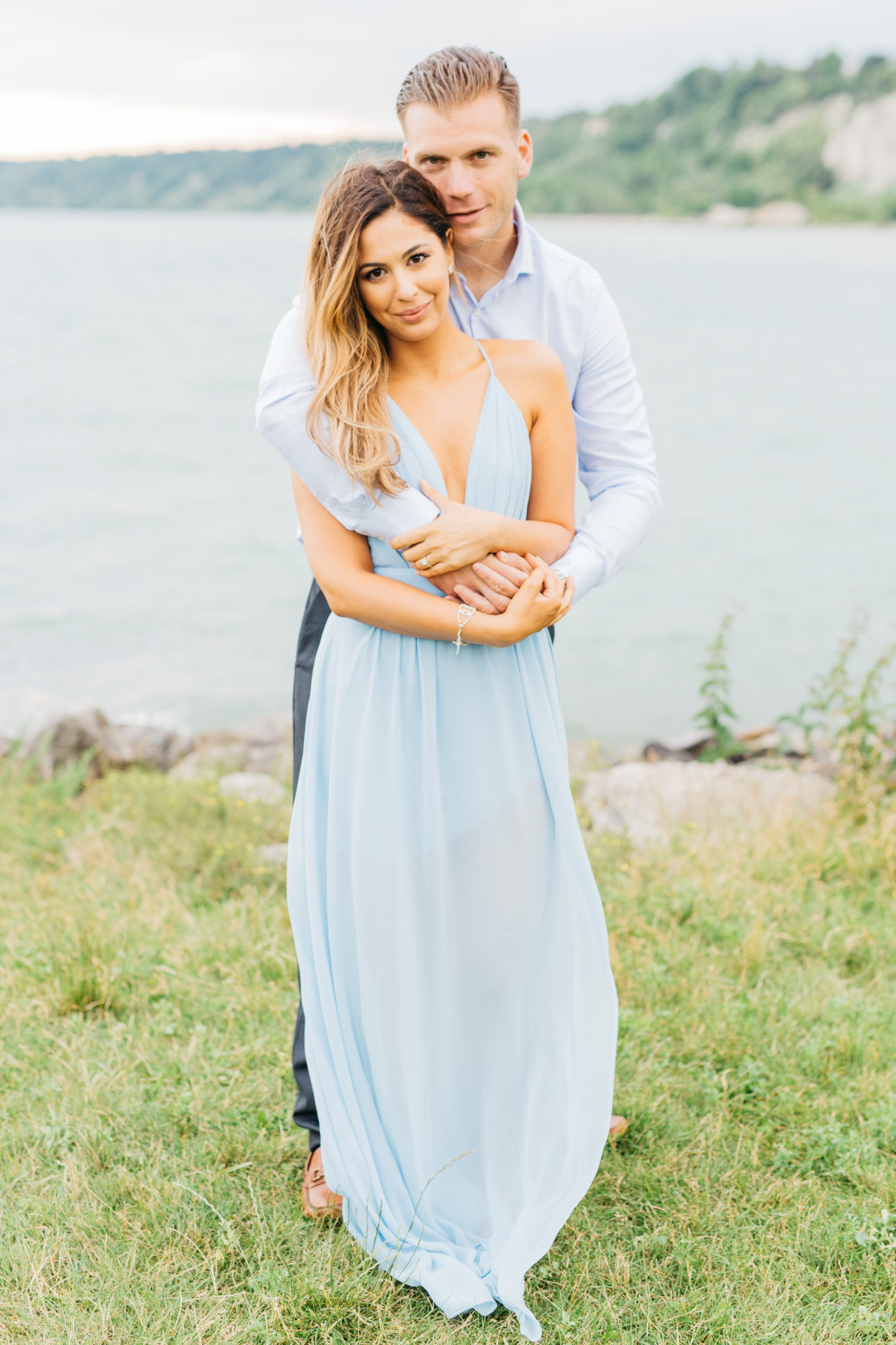 Couple cuddling during engagement session at Scarborough Bluffs