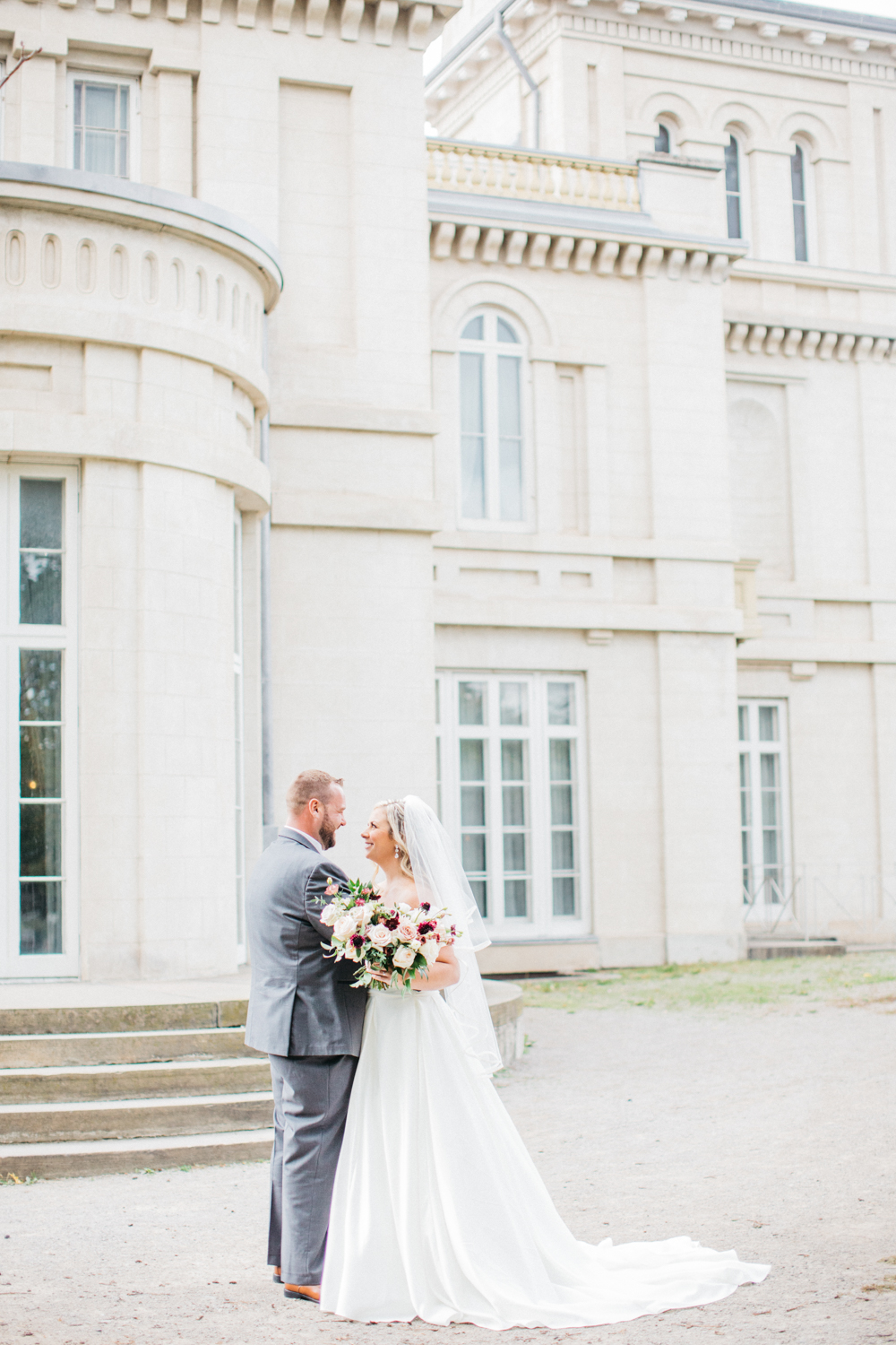 Bride and groom holding each other in front of Dundurn Castle