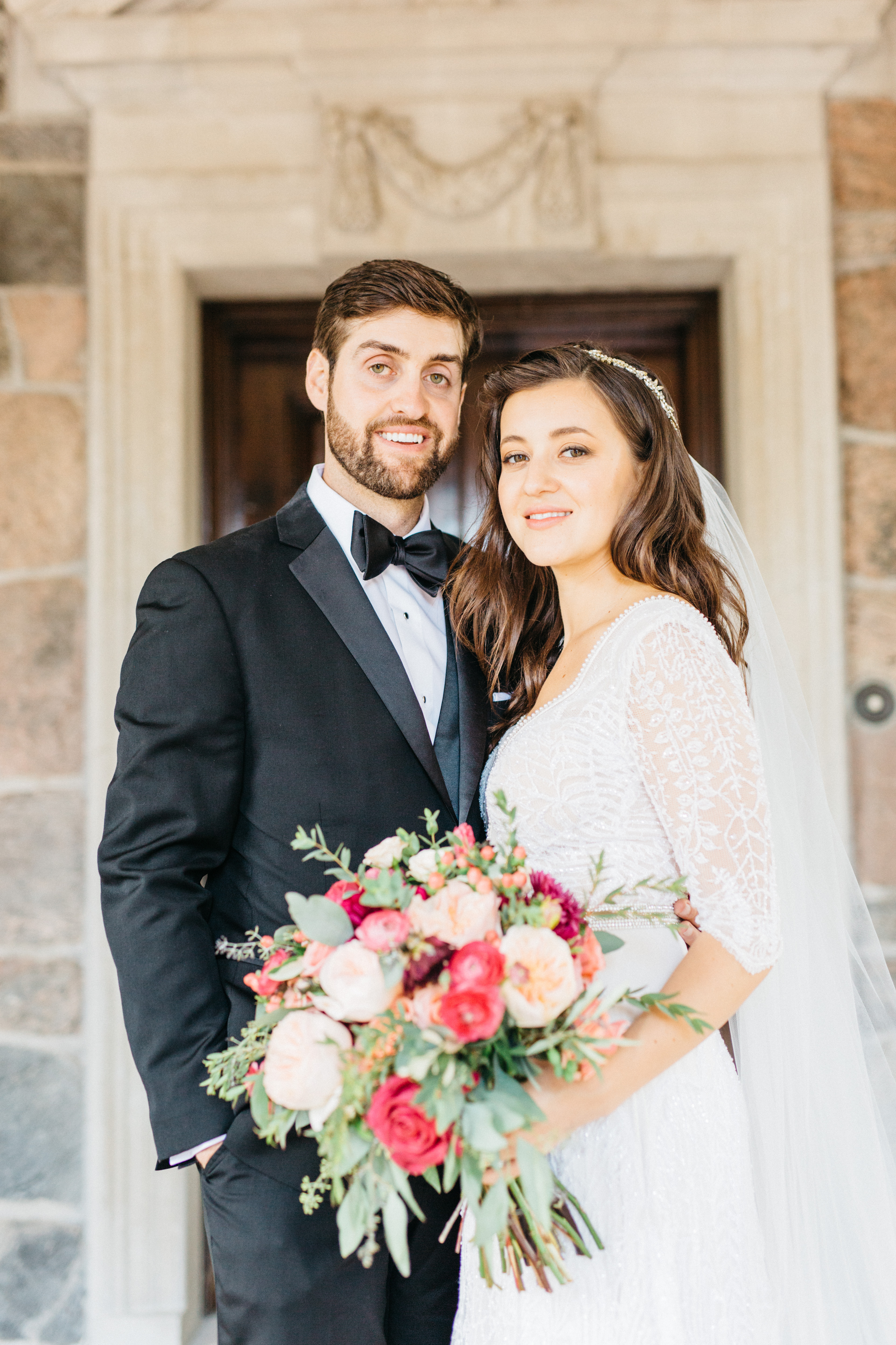 Bride and groom smiling at front steps at Graydon Hall Manor
