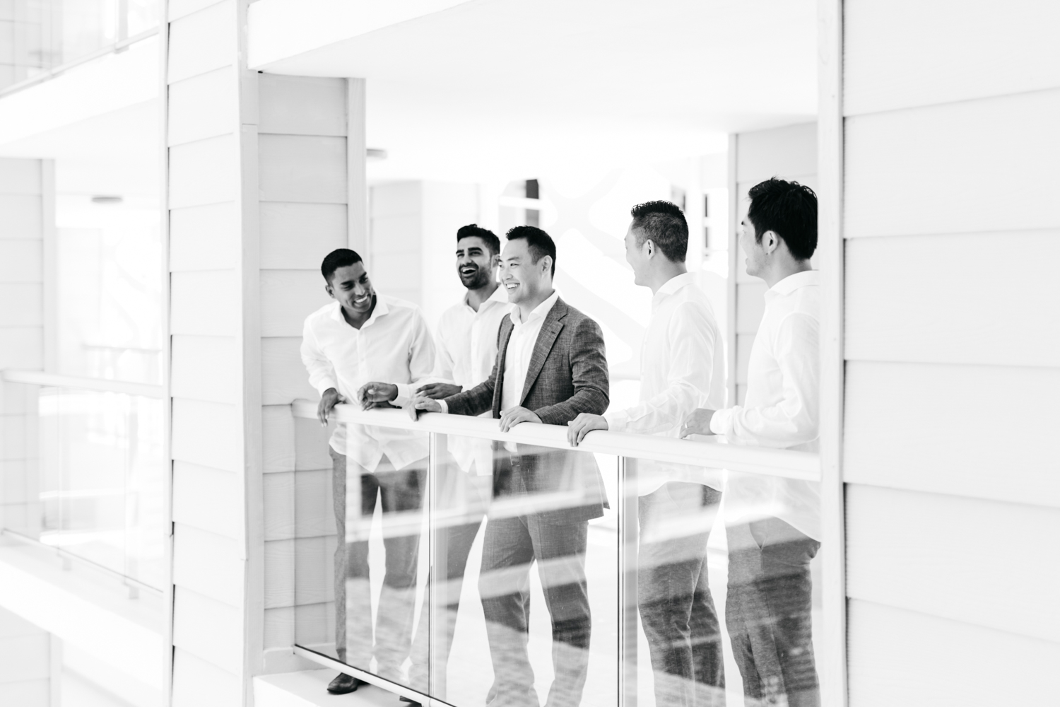 Groom laughing with groomsmen on balcony at Royalton White Sands Resort in Jamaica