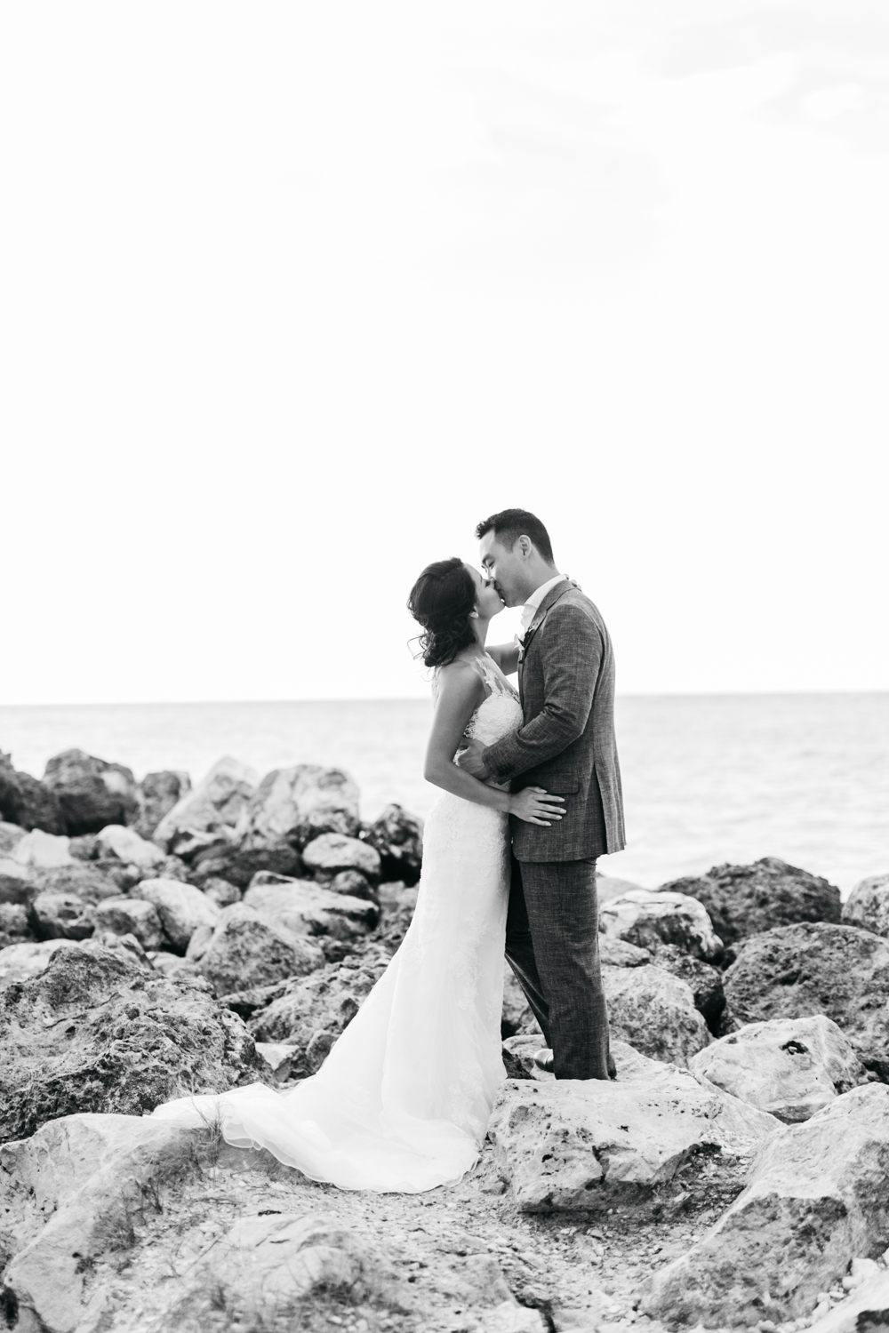 Bride and groom kissing on rocks at Royalton White Sands Resort in Jamaica
