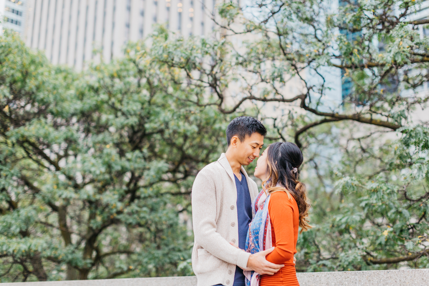 Couple cuddling during fall engagement at Nathan Phillips Square