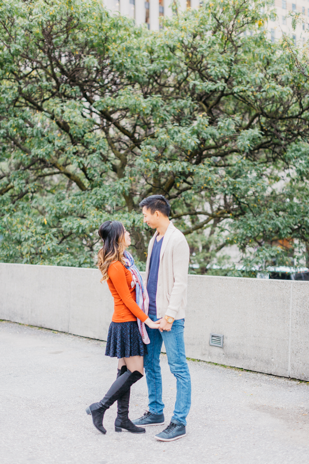 Couple holding hands during engagement at Nathan Phillips Square