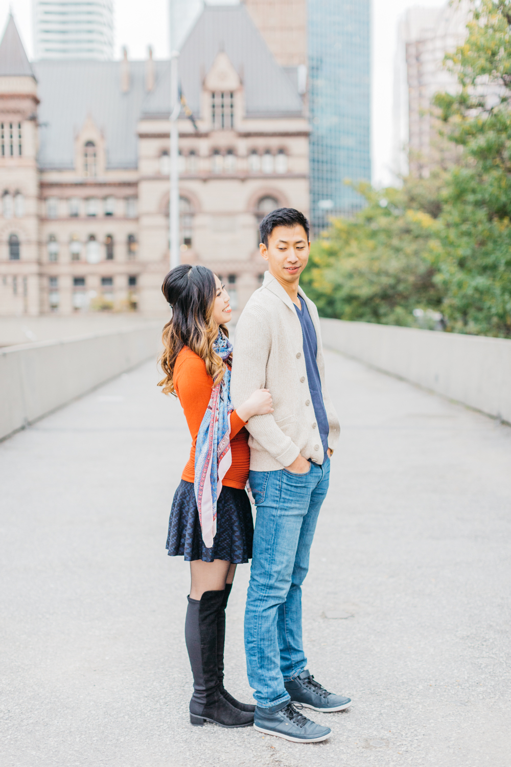 Couple cuddling during engagement at Nathan Phillips Square