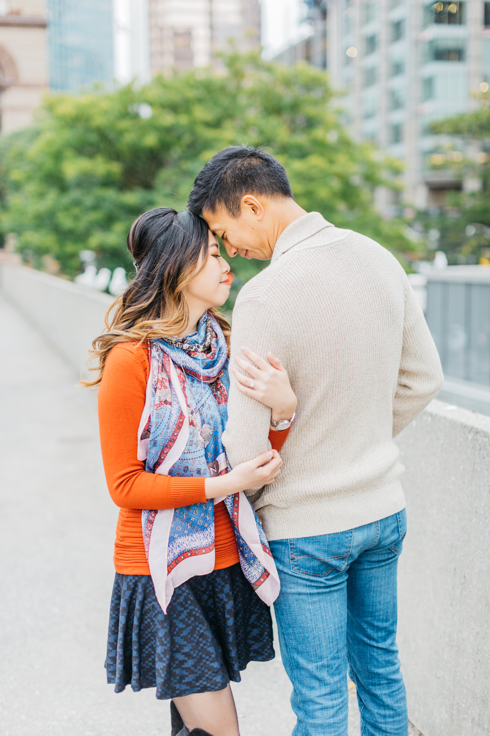 couple cuddling at Nathan Phillips Square engagement