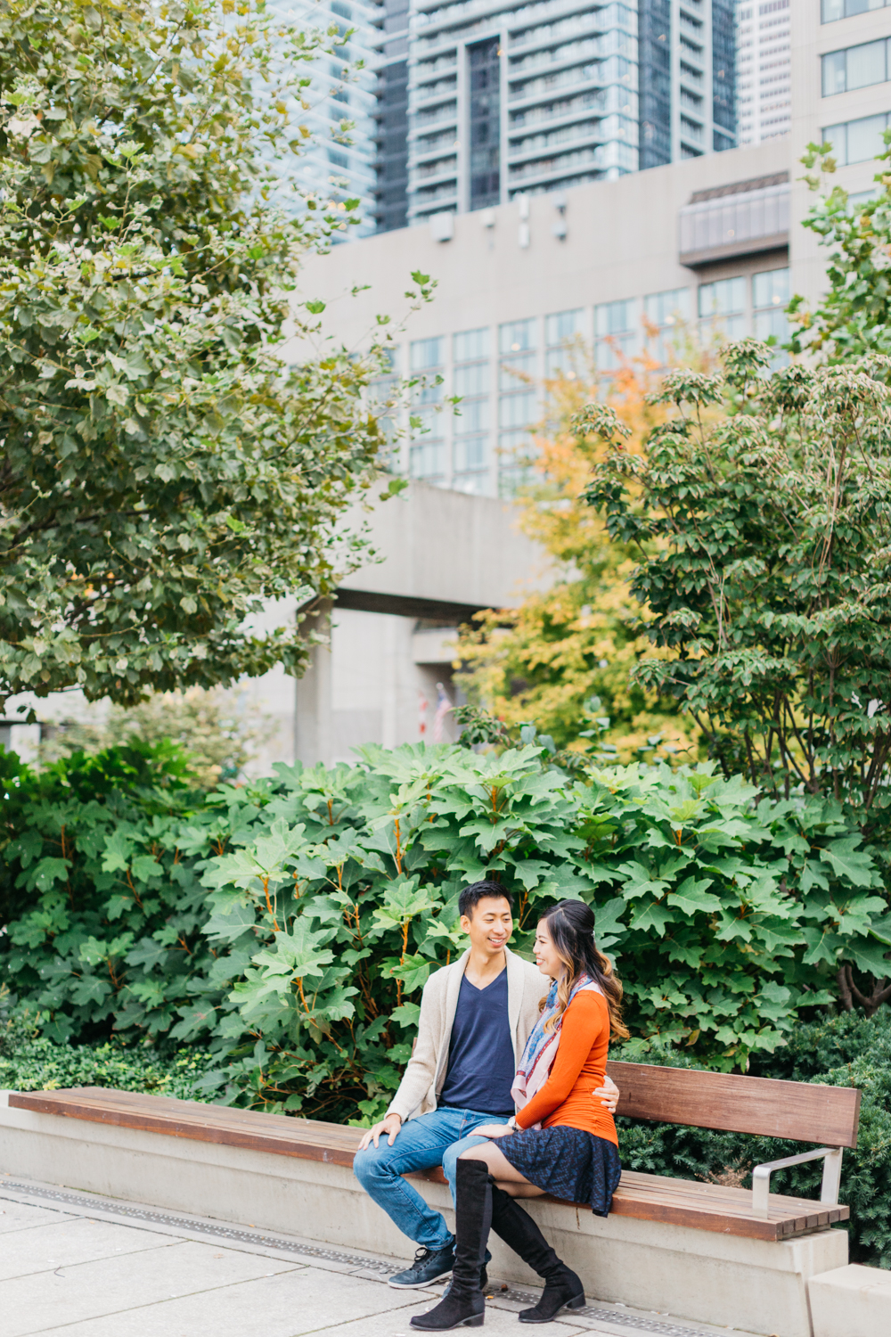 Couple talking on bench during fall engagement shoot at Nathan Phillips Square