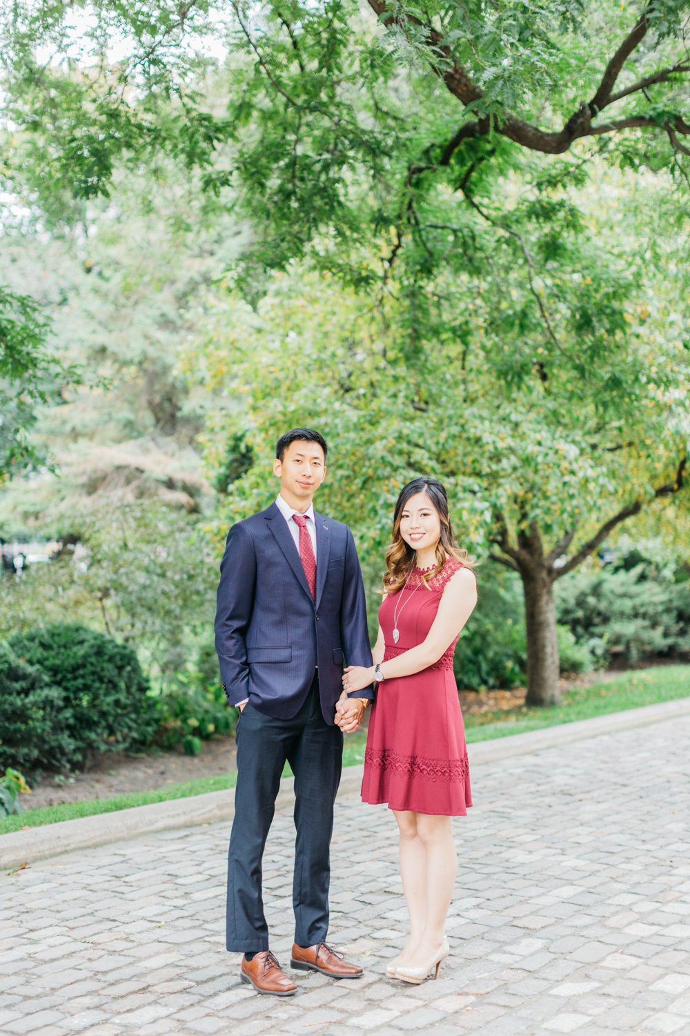 Couple holding hands during fall shoot at Osgoode Hall