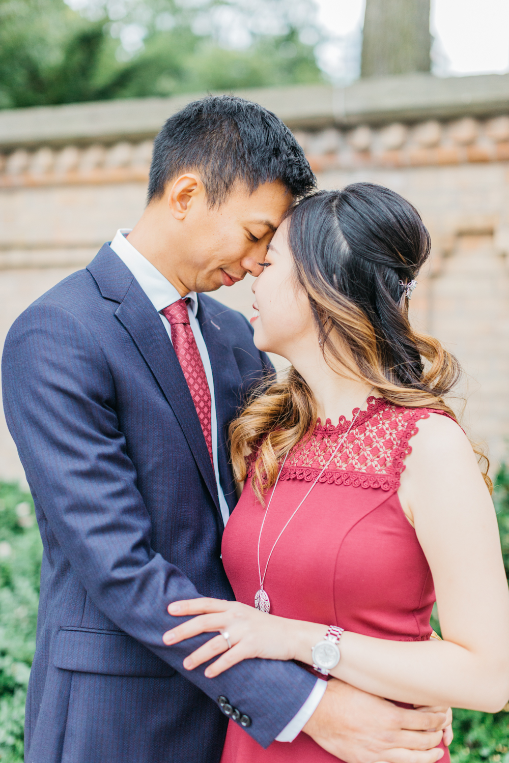 Couple cuddling during romantic fall engagement at Osgoode Hall